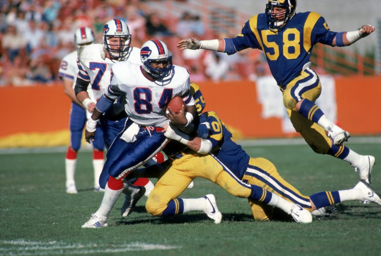 Tight end Buster Barnett of the Bills tries to break away from a tackle as linebacker Mel Owens (58) of the Los Angeles Rams closes on him from during a game at Anaheim Stadium on Nov. 27, 1983 in Anaheim. It was the Bills last game against the Rams in California. (Getty Images)