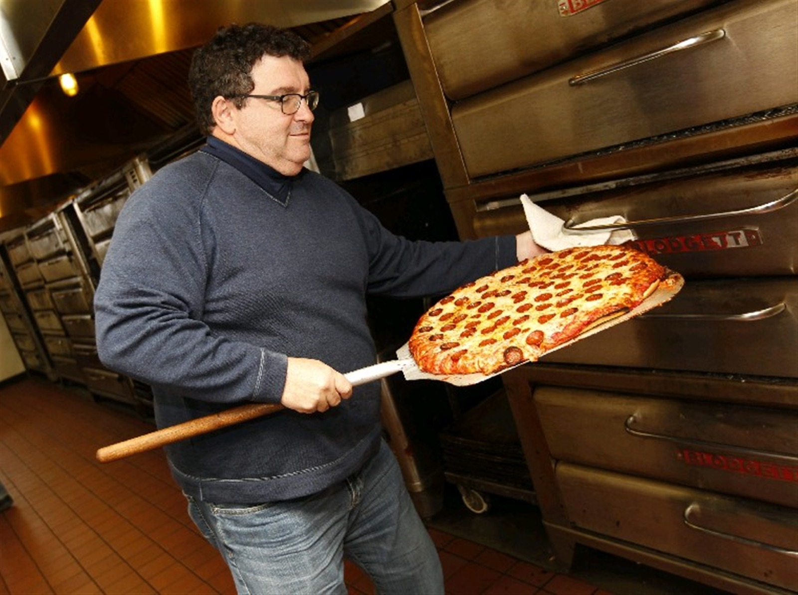A cheese-and-pepperoni pie from Bocce Club Pizza just after it exits the oven. (Sharon Cantillon/Buffalo News)