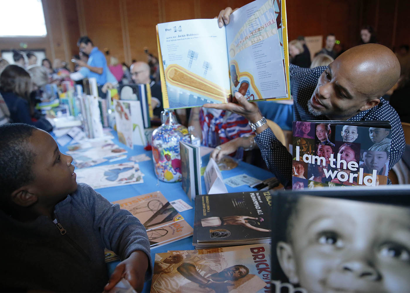 """Author Charles R. Smith Jr. holds up a copy of his book """"28 Days: Moments in Black History that Changed the World"""" while telling young Joshua Bell, 4, of Buffalo about baseball player Hank Aaron at the WNY Children's Book Expo at Kleinhan's Hall, Sunday, Nov. 6, 2016. (Derek Gee/Buffalo News)"""