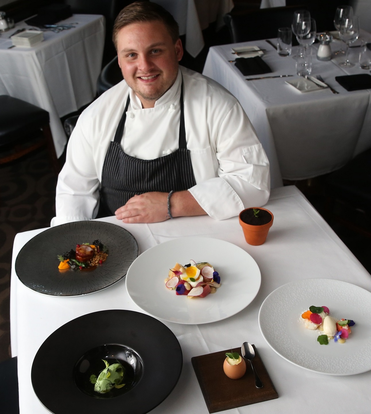 Executive chef Ross Warhol sits in front of several colorful plates at Oliver's. (Sharon Cantillon/Buffalo News)
