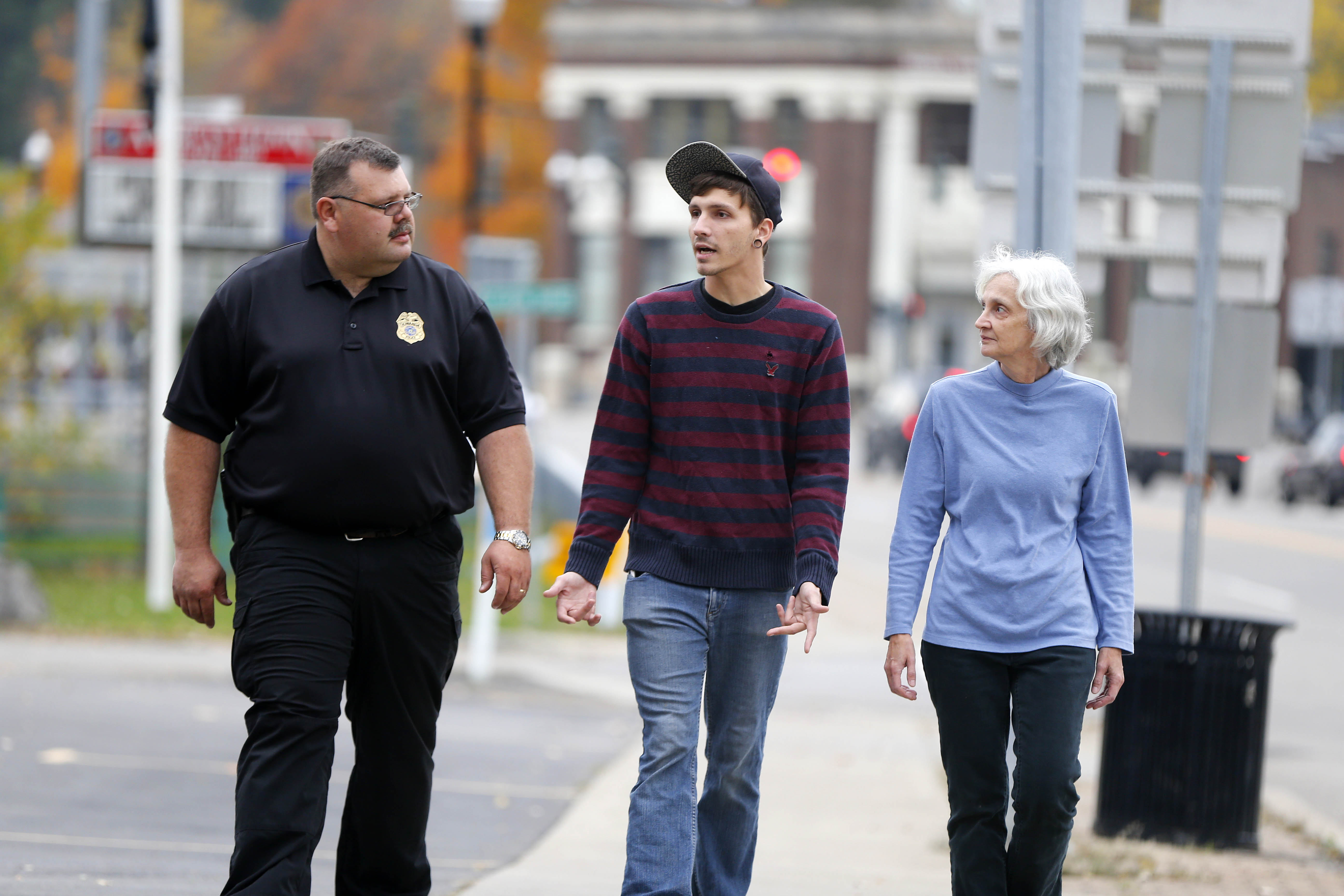 Gowanda Police Officer Steve Raiport, left, talks with Michael Witherell, center, and his mother Gloria Witherell, right, on Main St in Gowanda Wednesday, Nov. 2, 2016.   (Mark Mulville/Buffalo News)