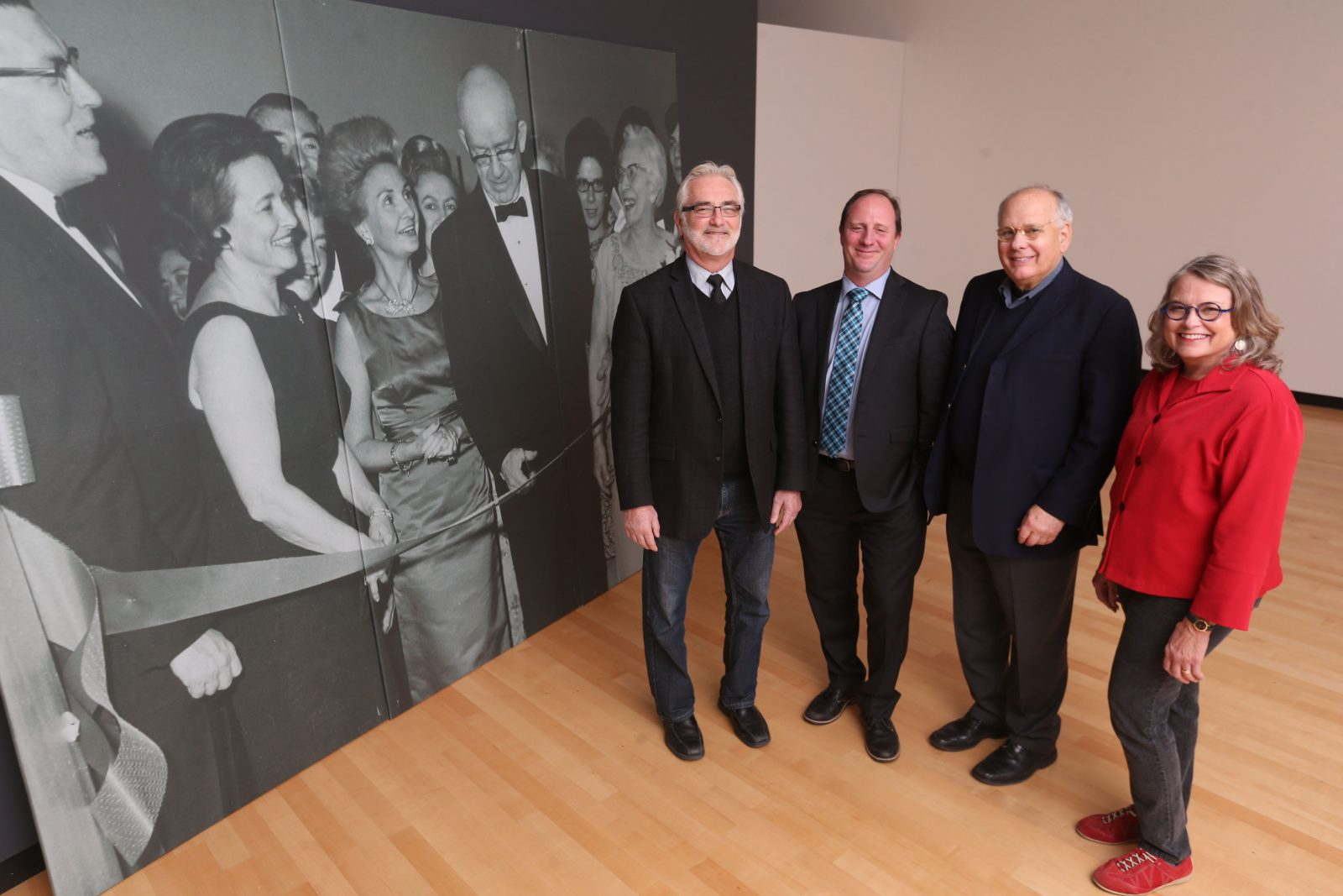 The Burchfield Penney is celebrating its 50th anniversary,  It's re-creating the first exhibition to mark the occasion.  Burchfield staff stand in front of a photo of the opening of the Charles Burchfield Center in 1966. Burchfield staff from left are Associate Director of Public Programming, Don Metz, Chief Curator Scott Propeack, Director Anthony Bannon and Burchfield Scholar Nancy Weekly. (Sharon Cantillon/Buffalo News)