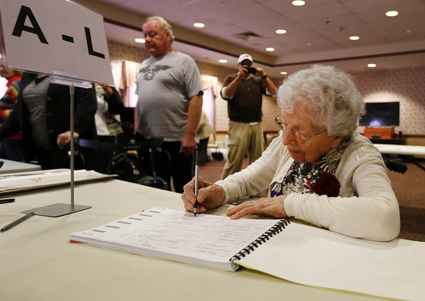 Helen Allen, 108 years old, was born before women had the right to vote, signs in before casting her ballot in this years election at Elderwood in Wheatfield with some assistance from Excecutive Director Shannon Cayea Tuesday, Nov. 8, 2016. Allen remembers when her mother voted for the first time. (Mark Mulville/Buffalo News)