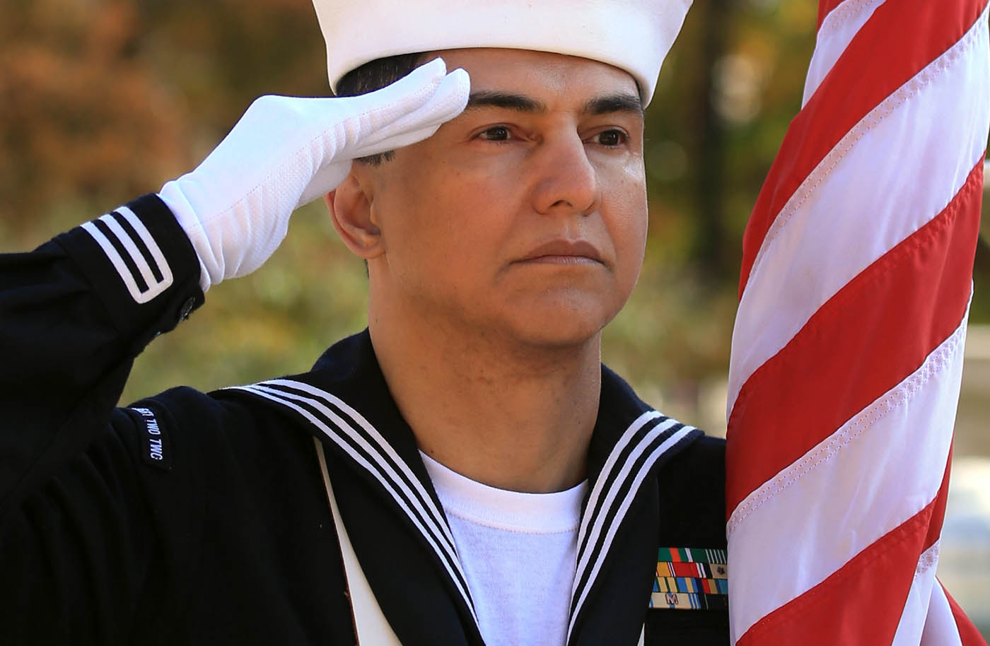 Petty Officer 2nd Class Miguel Reys a U.S. Navy Reservist and member of the color guard salutes during the national anthem at a Veterans day parade celebration at Niasgara Square in Buffalo, N.Y. on Saturday, Nov. 5, 2016. (John Hickey/Buffalo News)