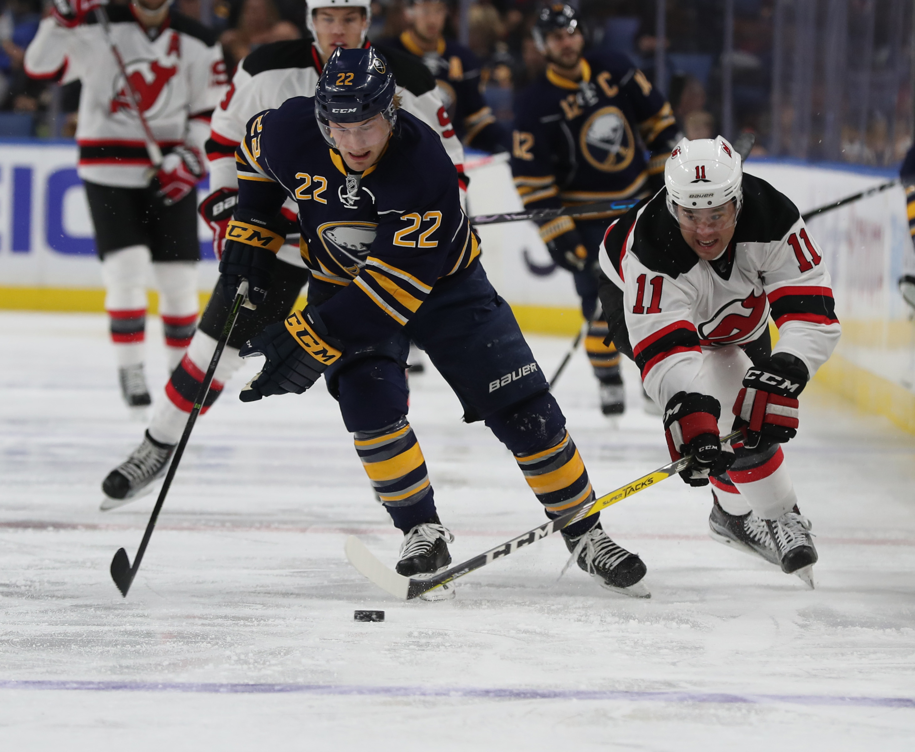Sabres center Johan Larsson (22) battles New Jersey winger PA Parenteau (11). (James P. McCoy/Buffalo News)