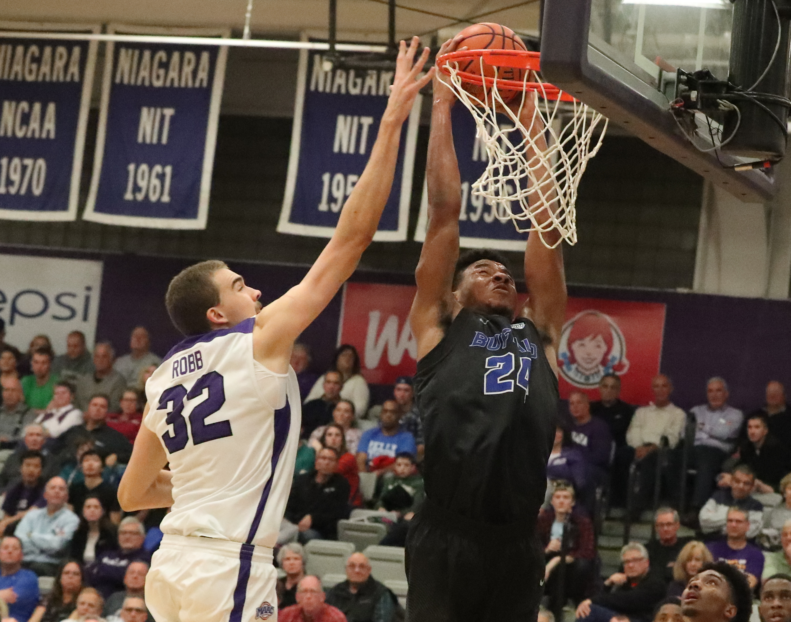 Buffalo Bulls forward Quate McKinzie dunks over Niagara's Dominic Robb in the second half at Gallagher Center Friday (James P. McCoy/Buffalo News)