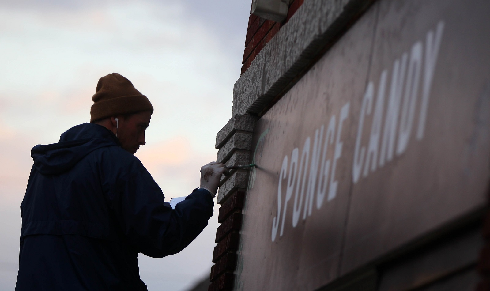 Jon Daly works on painting the store sign at Ko-Ed Candies. (Mark Mulville/Buffalo News)