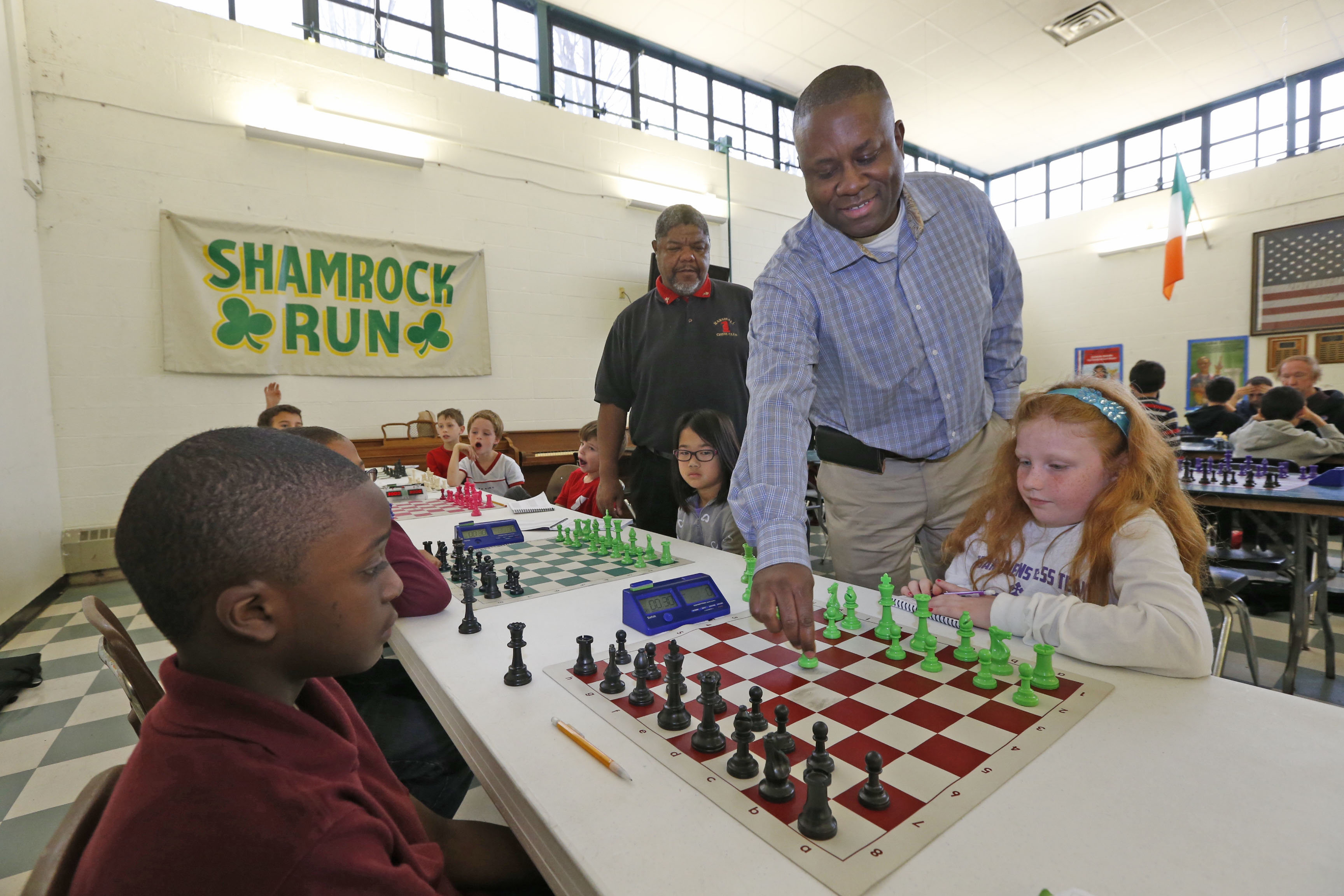 First-ever cup champion and author Eddie Mack moves one of Sami Woods' pieces, right, who was playing Jimmir Darby, takes the ceremonial first-move at the Mayor's Cup Chess Championship. (Robert Kirkham/Buffalo News)
