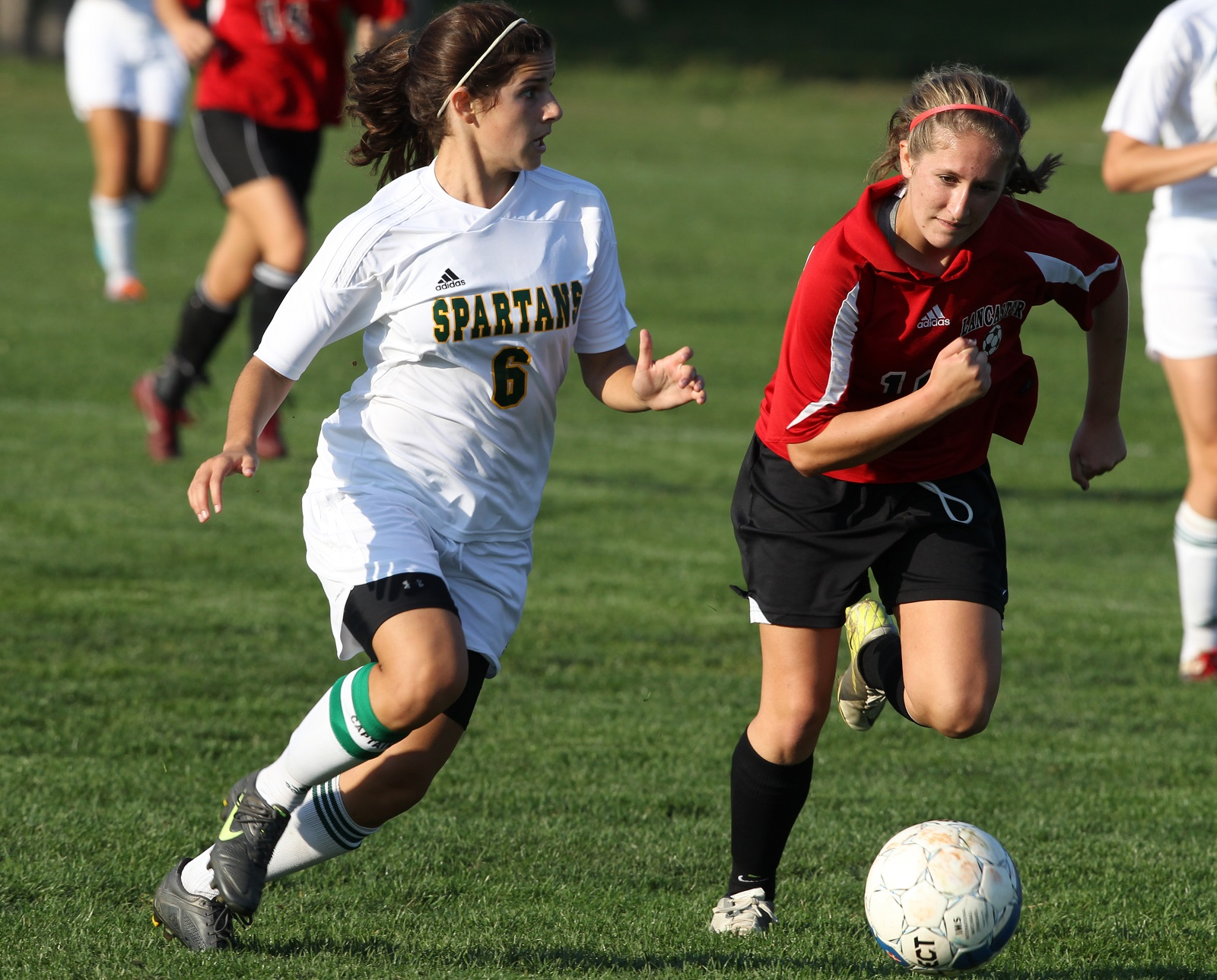 Williamsville North's Meredith Licata, left, races for a ball against Lancaster's Kailee Juzdowski in 2012. Licata now stars for Trinity College, while Juzdowski earned AMCC honors with D'Youville. (James P. McCoy/Buffalo News file photo)