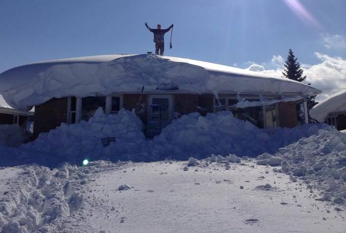 Conor Deubell shovels off the roof of his grandmother's house on Whitfield Avenue in South Buffalo.