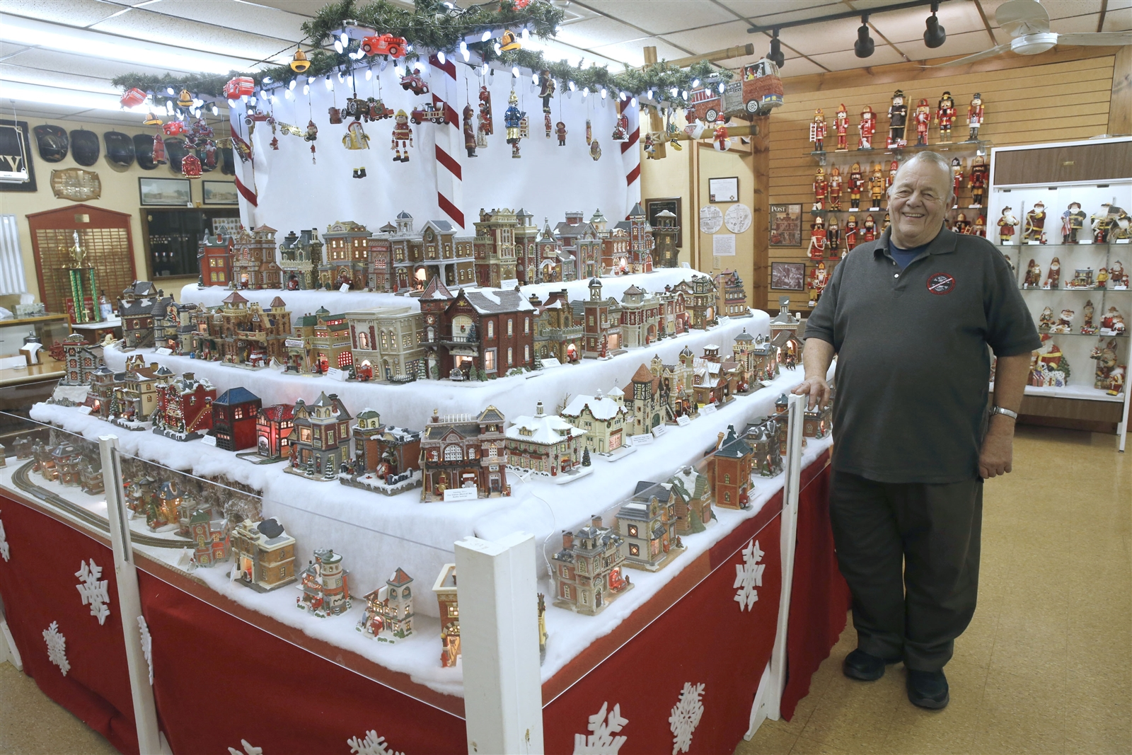 Pat Coghlan, president of the Buffalo Fire Historical Society, stands by vintage ceramic firehouses that are part of a holiday display at the museum. (Robert Kirkham/Buffalo News)