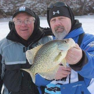 Scott Brauer of Gasport (R) hoists up a nice crappie with ice fishing legend Dave Genz of Minnesota looks on.