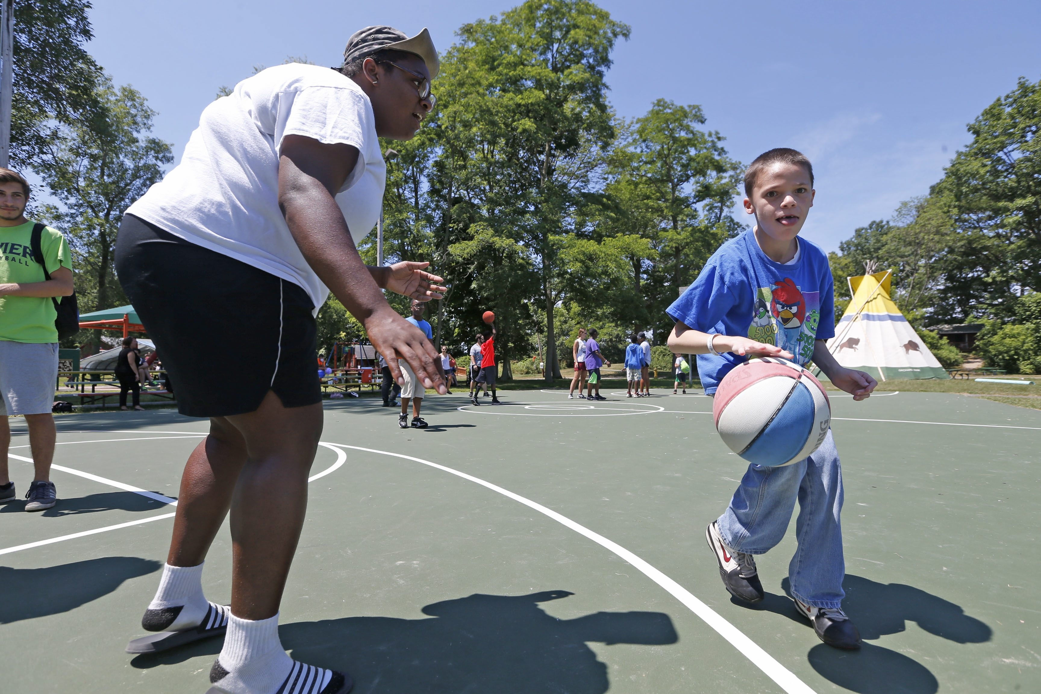 Counselor Briana 'BriZ' Harris, left, plays some one-on-one basketball with camper Kenny Skutt, 12, of Lackawanna at Cradle beach in Angola on Monday, July 11, 2016.  (Robert Kirkham/Buffalo News file photo)