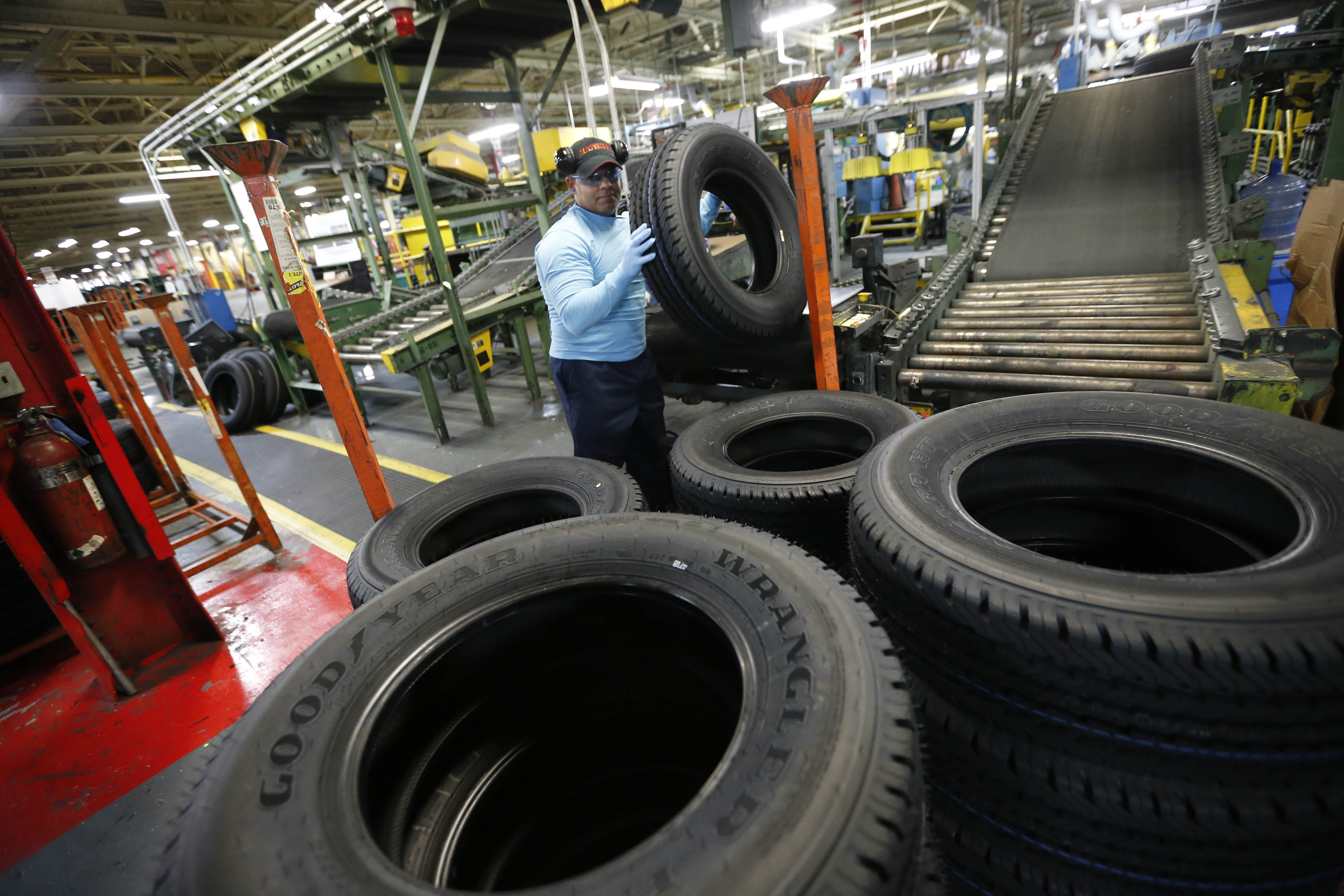 A worker pulls a truck tire off of the curing line at the Sumitomo Rubber USA tire manufacturing plant in Tonawanda.  (Derek Gee/Buffalo News)
