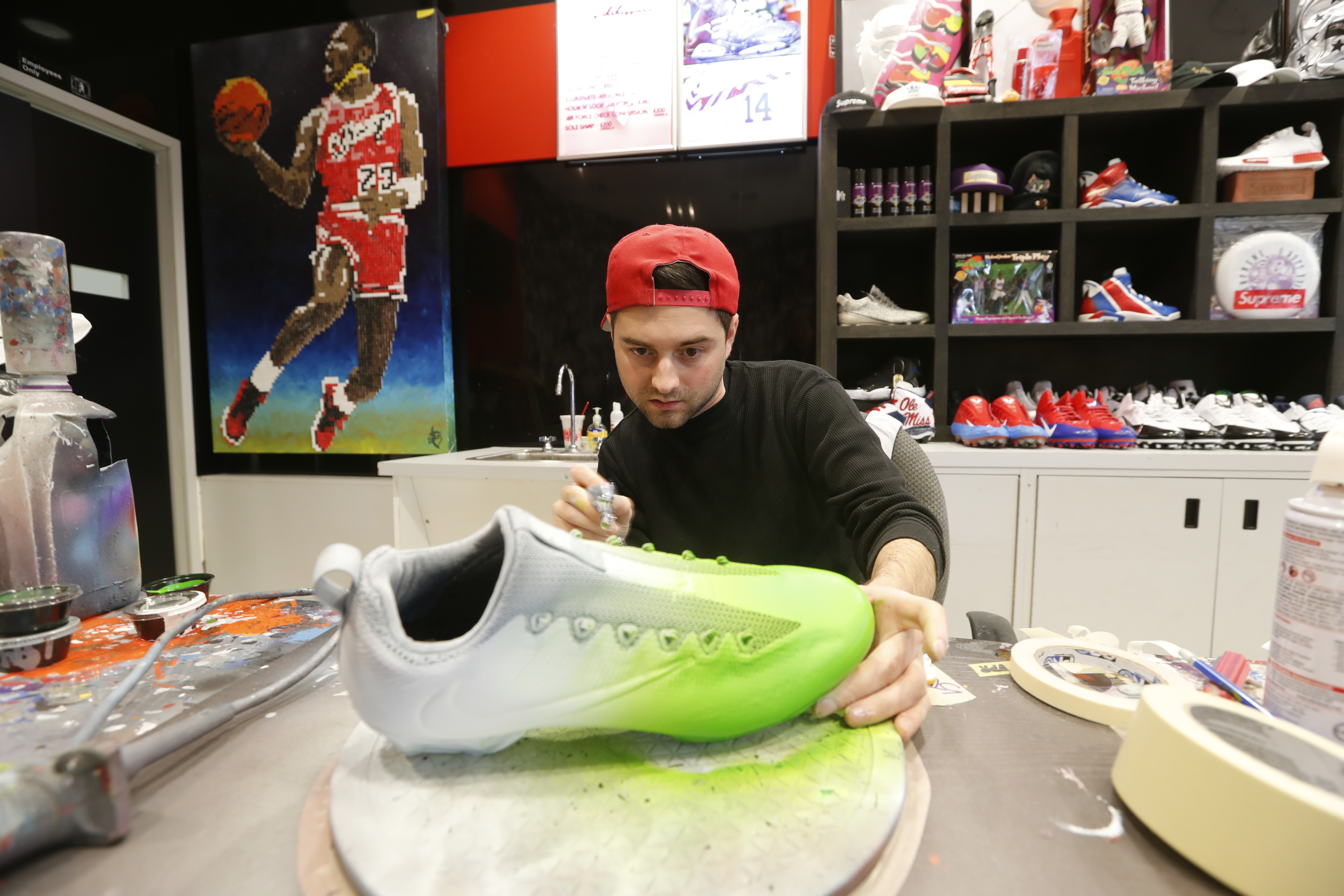 Nicholas Avery works on a pair of cleats for Marquise Goodwin of the Buffalo Bills. (Harry Scull Jr./Buffalo News)
