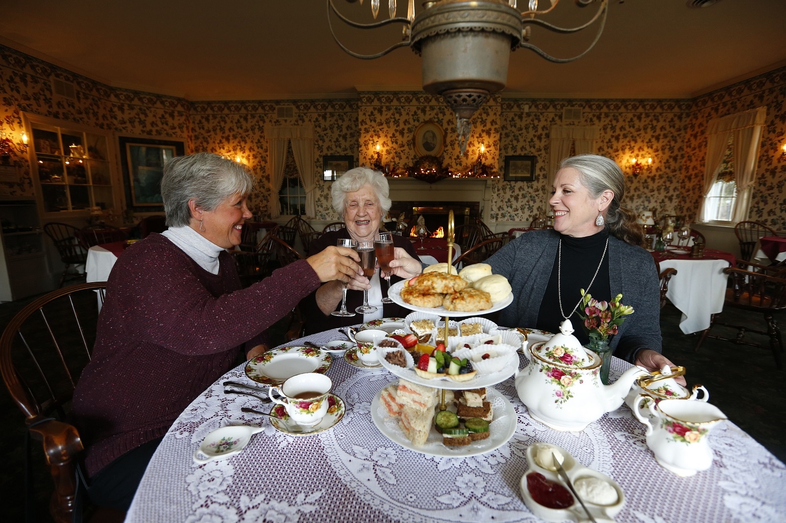Sue Barth, left, and Lynn Minter, right, do a champagne toast with their mother, Marge Jamson, for her birthday during a tea at the Asa Ransom House. The tea is offered all year long, but is especially nice for gathering with friends and family around the holidays. (Mark Mulville/The Buffalo News)