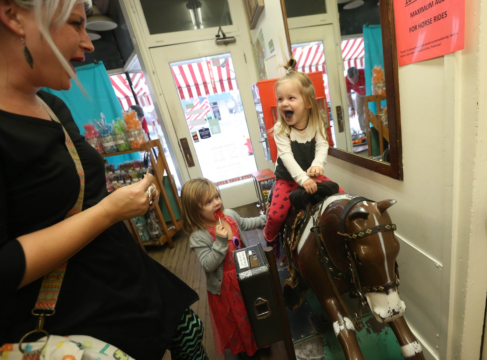 Audrey Slanovich of East Aurora puts in a dime into the mechanical horsey, so her daughter Betty can ride it. The ride is more robust than she expected.  Looking on is her sister Leora, 4. (Sharon Cantillon/Buffalo News)