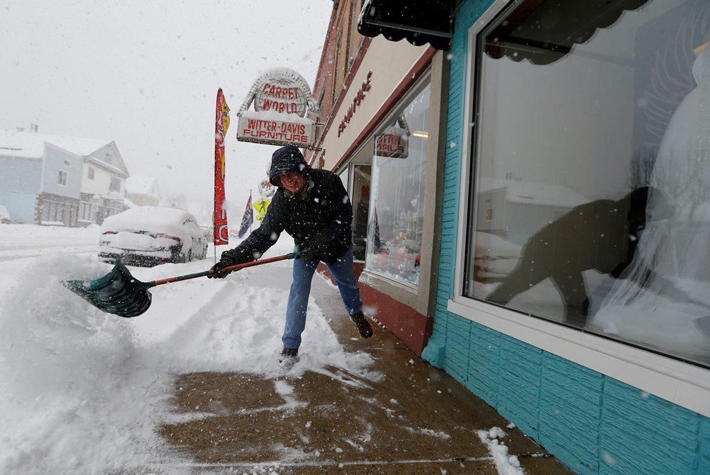Joe Decker shovels the sidewalk in front of his business on Main Street in Springville Thursday, December 8, 2016.    (Mark Mulville/The Buffalo News)