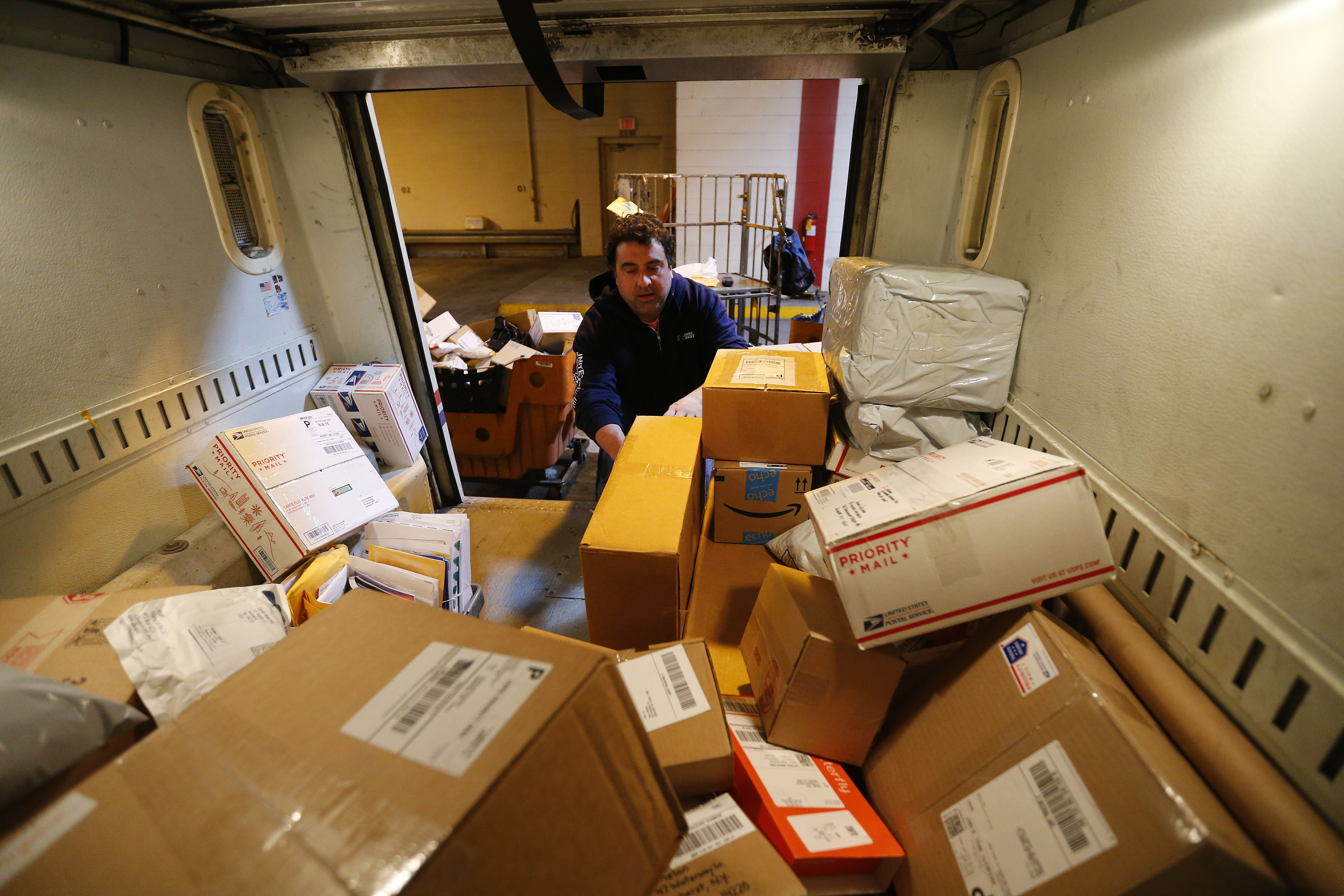 Gary Cascio loads his delivery truck with letters and packages at the post office on North Bailey in Amherst Monday, Dec. 19, 2016. (Mark Mulville/Buffalo News)