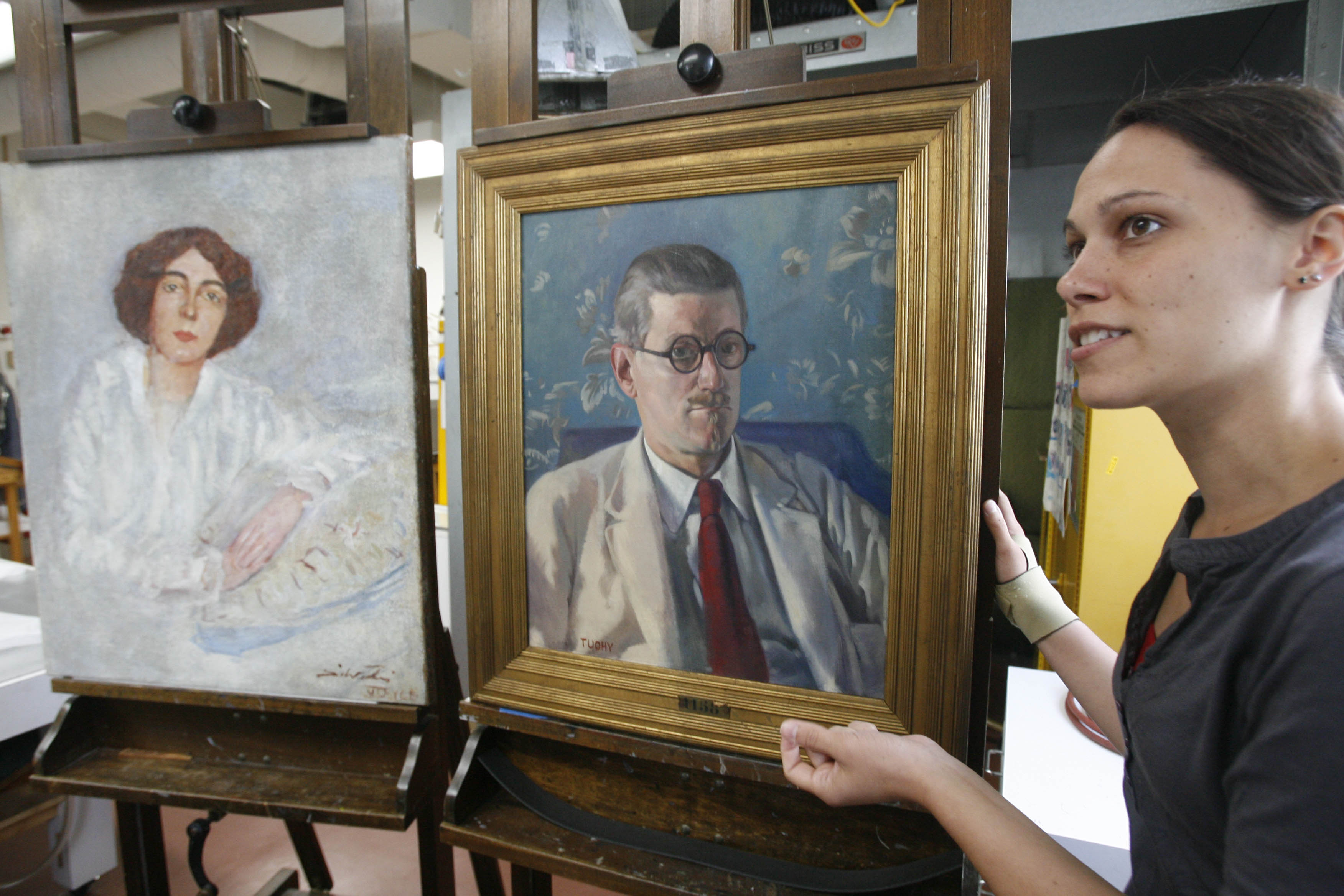 In 2008, Buffalo State College art conservation graduate student Katrina Bartlett explains the restoration work she did on paintings of author James Joyce and his wife Nora – two of nine paintings from Joyce's collection restored in the department. (Derek Gee/Buffalo News)