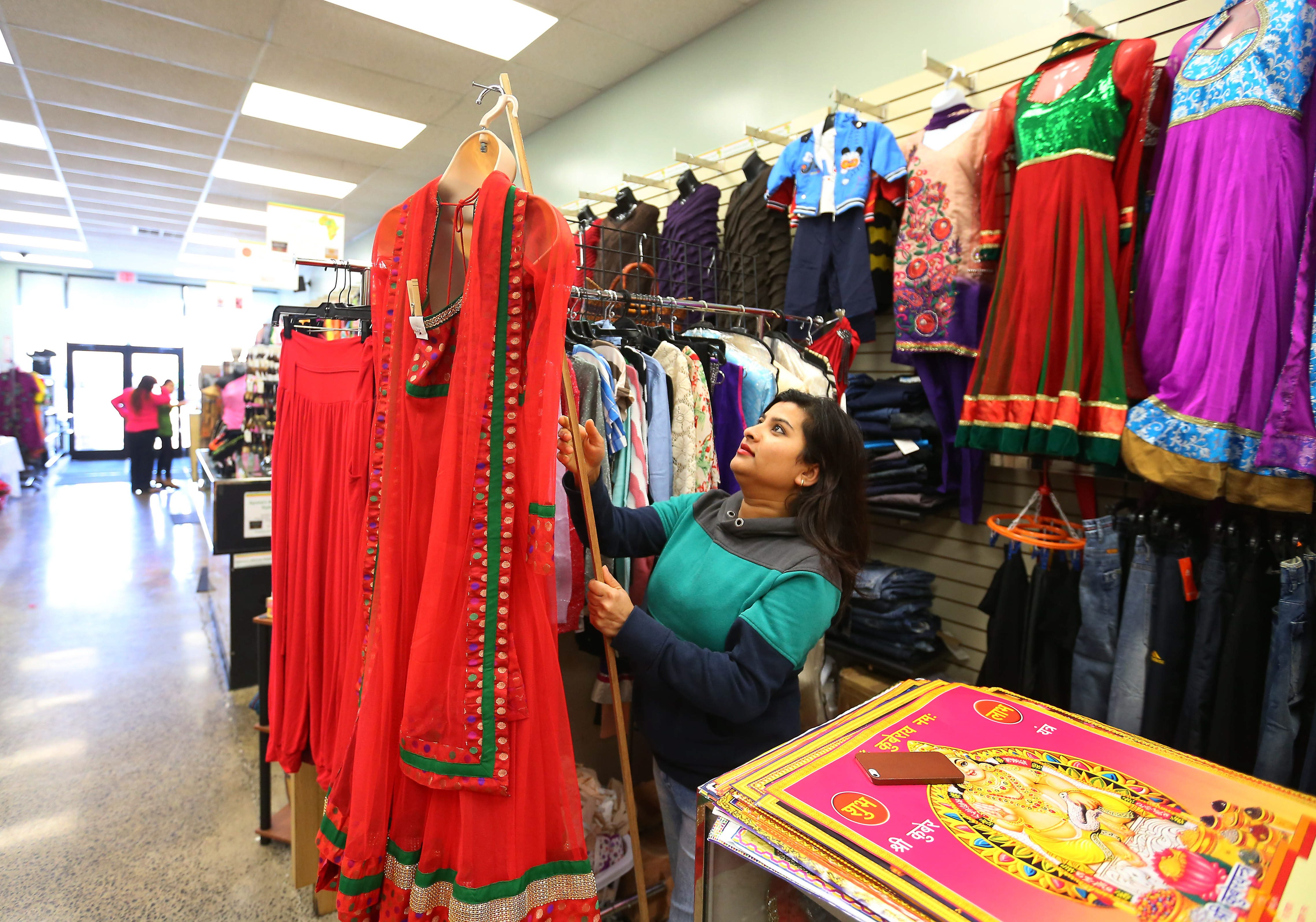 Madhavi Pyakurel hangs a Kurta Shawler from Nepal at her stand in the West Side Bazaar on Grant near West Ferry St. in Buffalo Friday, October 24, 2014.  (Mark Mulville/Buffalo News)