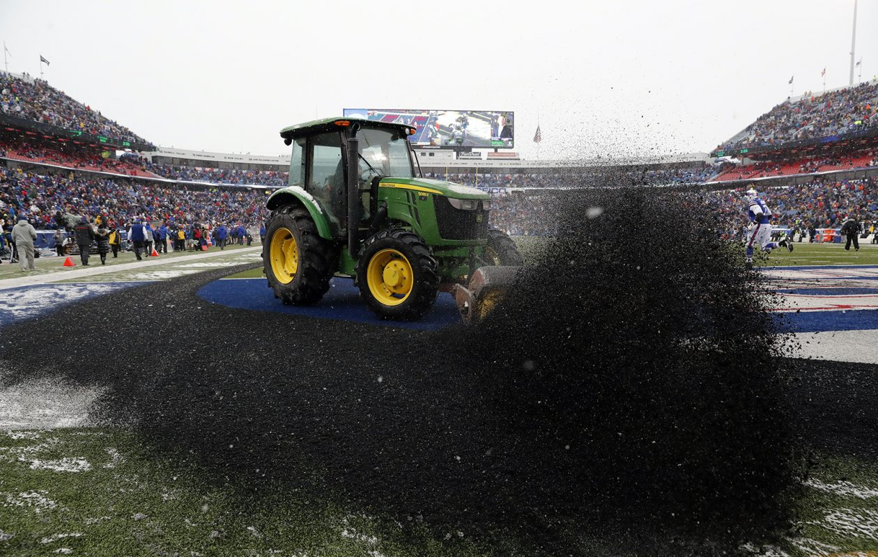 Tractors trying to clear New Era Field of snow sweep up piles of rubber turf pellets on Dec. 11, 2016. (Harry Scull Jr./News file photo)