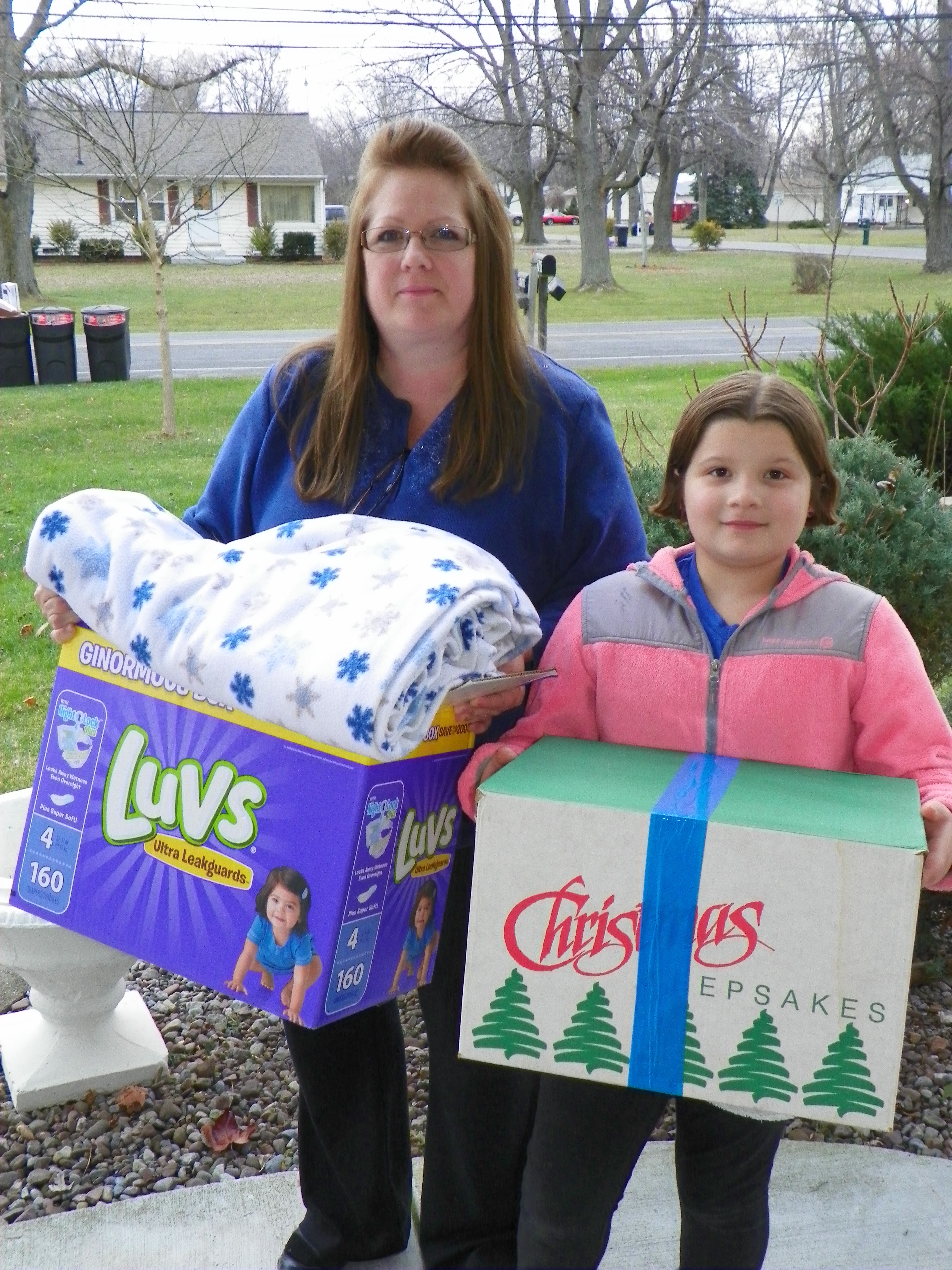 Denise Noble and her granddaughter, Savannah Robins, carry boxes of Christmas gifts to deliver to needy families in rural Niagara County during a prior year. (Provided photo).