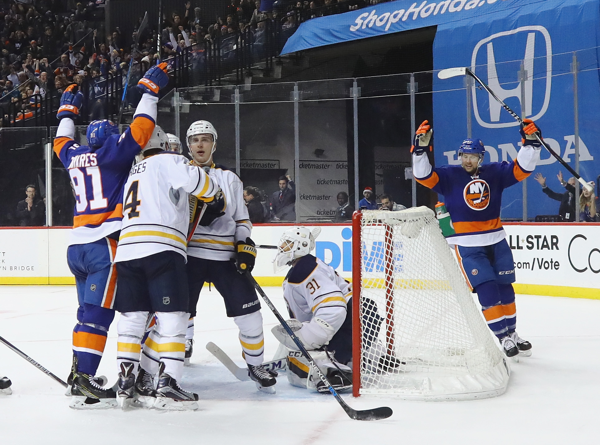 The Islanders' John Tavares (91) and Josh Bailey celebrated three New York goals during the first two periods. Josh Gorges (4), Rasmus Ristolainen and goalie Anders Nilsson had none. (Getty Images)