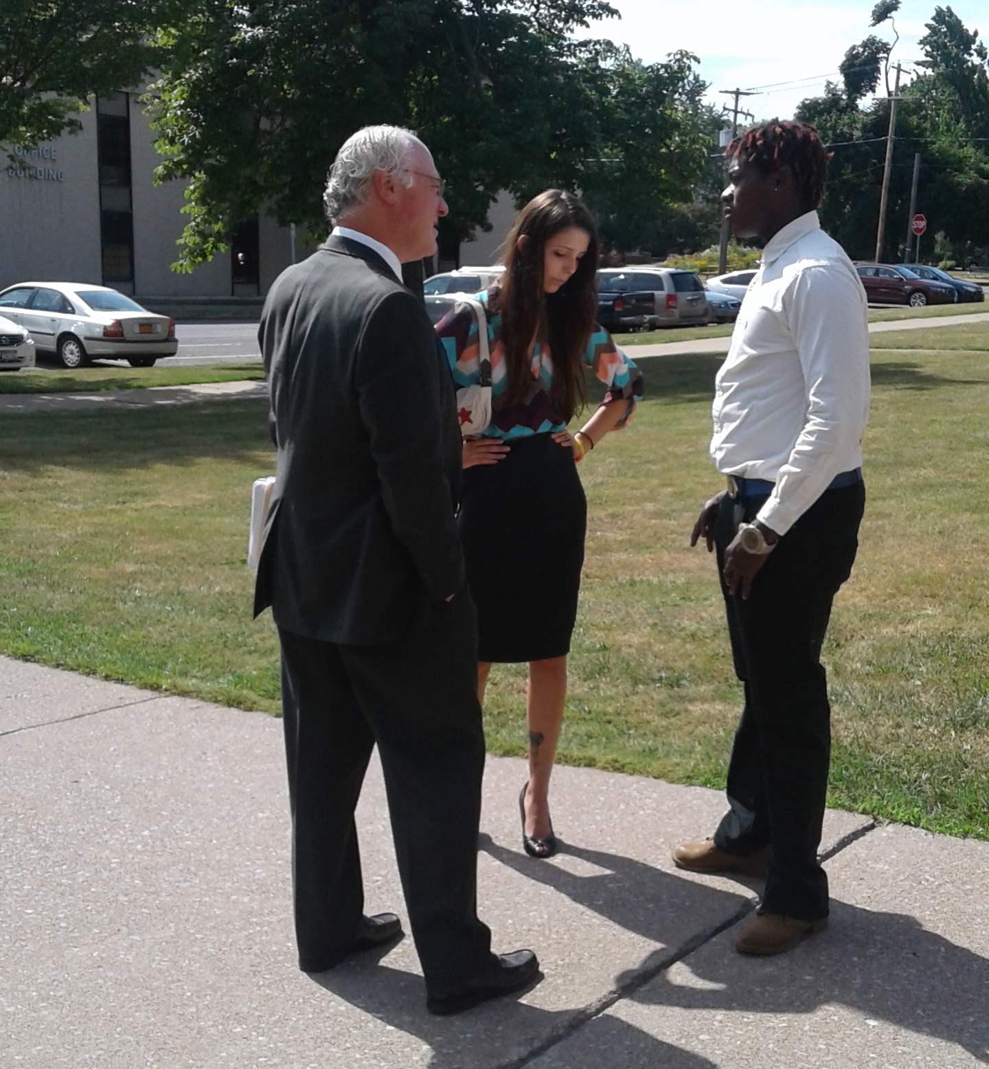 Gia M. Arnold, center, and Halim Johnson, right, confer with attorney James M. Ostrowski in Lockport on July 20, 2016. (Thomas J. Prohaska/Buffalo News)