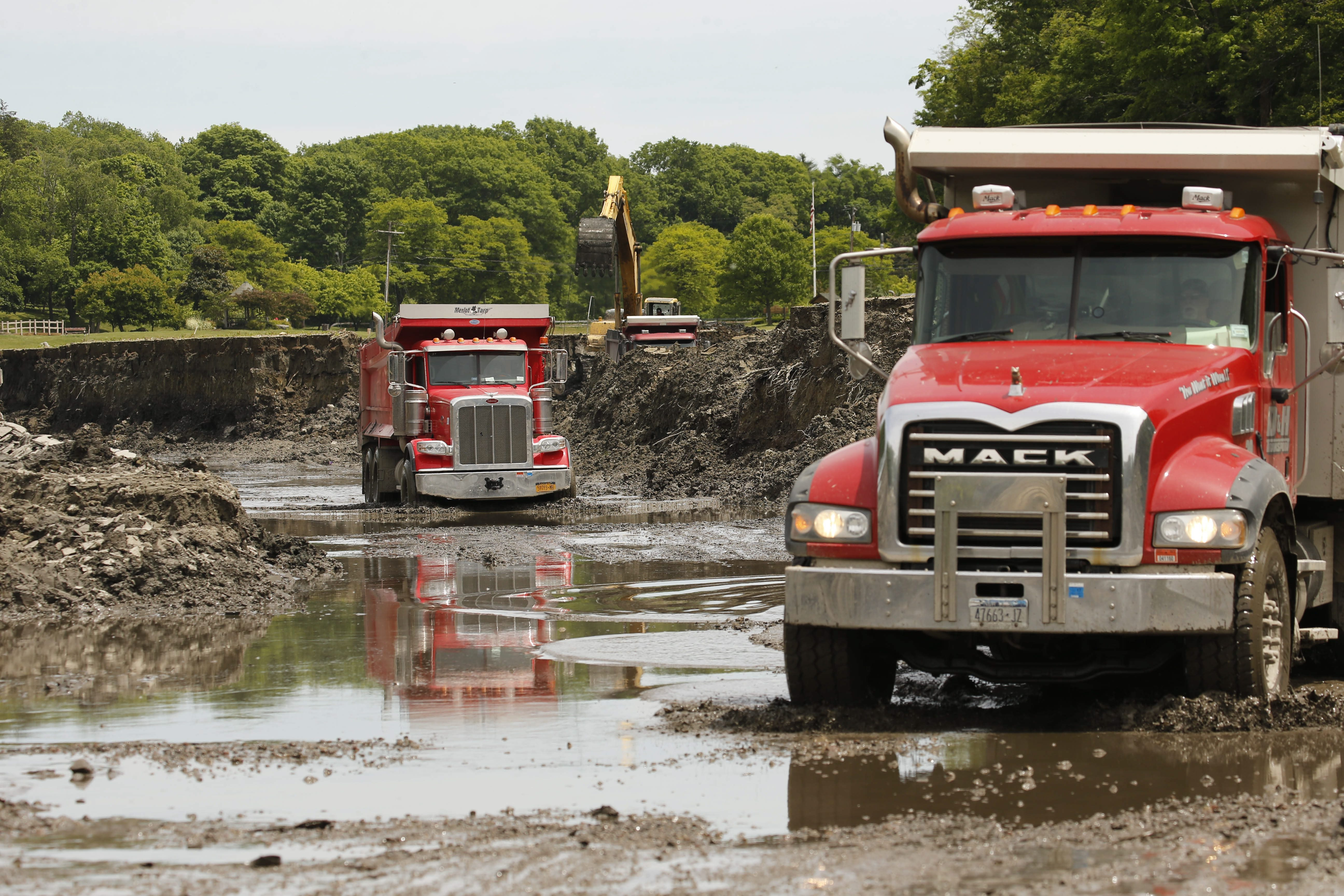 Dump trucks haul away sediment as crews excavate silt from the dried lake bed of Green Lake in Orchard Park on Friday, June 10, 2016. (Derek Gee/Buffalo News)