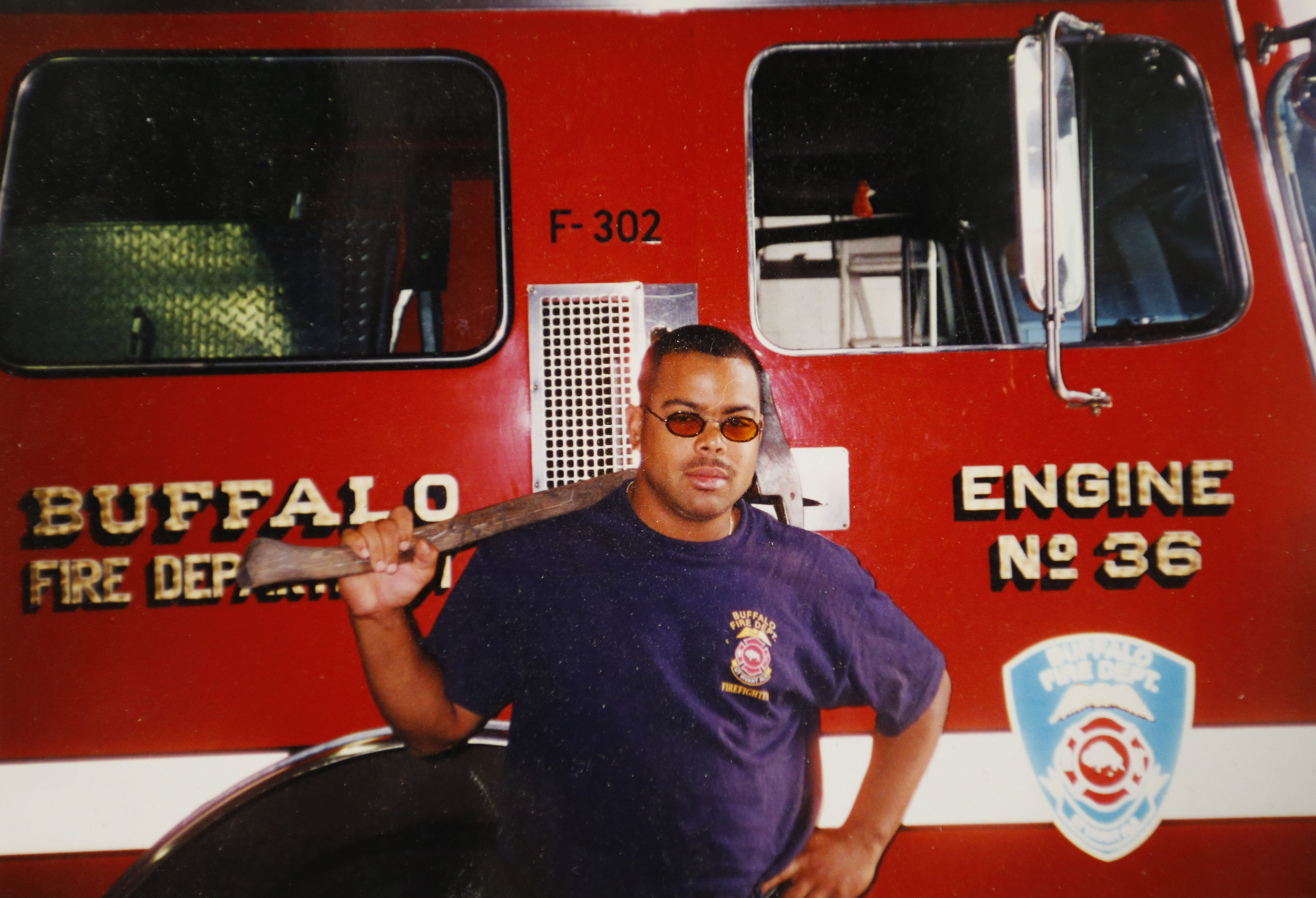 Buffalo firefighter Kristian T. Woods stands next to a fire truck in an undated family photo. Woods'  heart stopped in 2012 while he was in Erie County Sheriff's deputies custody and undergoing an apparent psychiatric crisis. Woods was revived, but remained in a coma for nearly six months until he died. (Courtesy of Kristian Woods' family)
