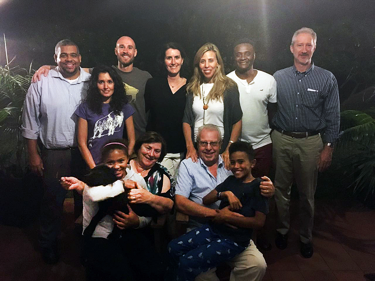 Western New Yorkers who enjoyed a holiday wing party in Nairobi are, front row, Sofia Kimuyu, holding Buddy, Christine Kurbiel, Roman Kimuyu on the lap of Steve Kurbiel; second row: Dr. Ben Piper from Lewiston, Dan Corrigan  from Williamsville, Jackie Corrigan from Grand Island, Sarah Skorupski from Buffalo, Lisa Kurbiel from North Tonawanda, Johnson Kimuyu, NT by marriage, and United States Ambassador Steven Schwartz from Williamsville.