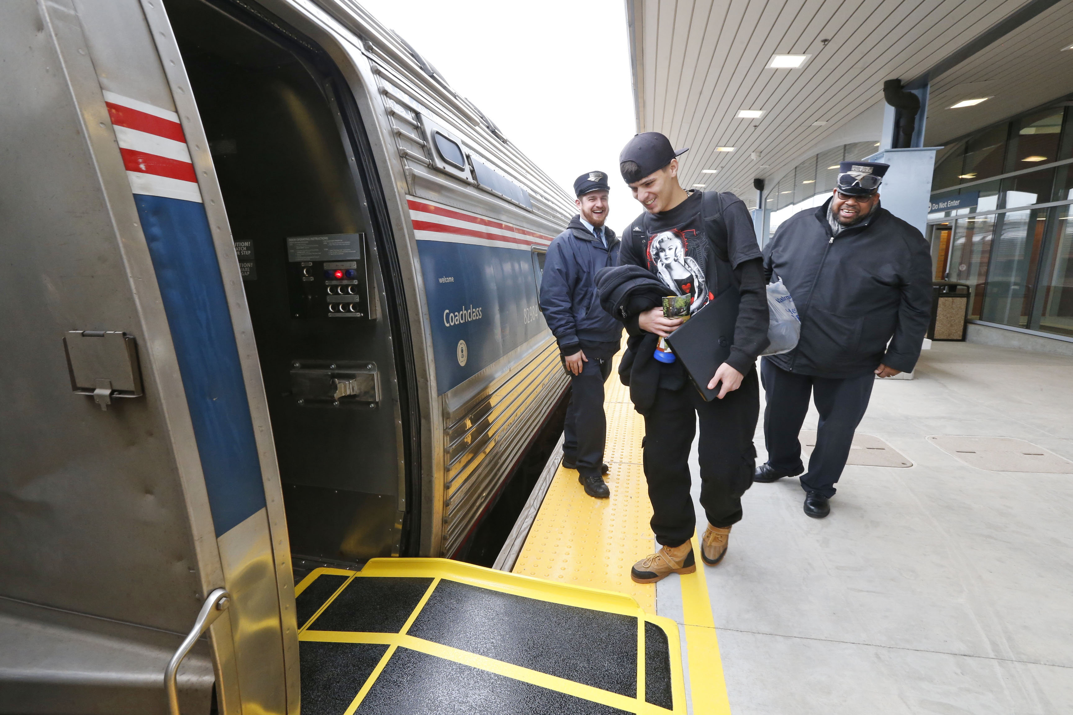 Amtrak conductors Greg Holoduek, left, and S. Johnson welcome Niagara Falls resident Luis Lopez aboard the first  train to depart from the new Amtrak station in Niagara Falls, N.Y., on   Tuesday, Dec. 6, 2016.  (Robert Kirkham/Buffalo News)