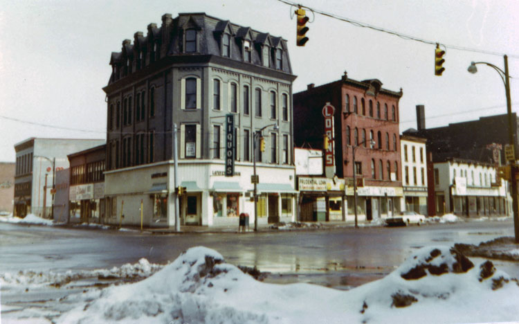 "At the top of the page is Charles Birchfield's ""Rainy Night"" (1929-30). This photo was one of many taken by artist James Vullo in the mid-70's depicting the real life places depicted in Burchfield's paintings and sketches. (Charles E. Burchfield Archives) Below, the intersection of Ellicott and Broadway as it looks today."