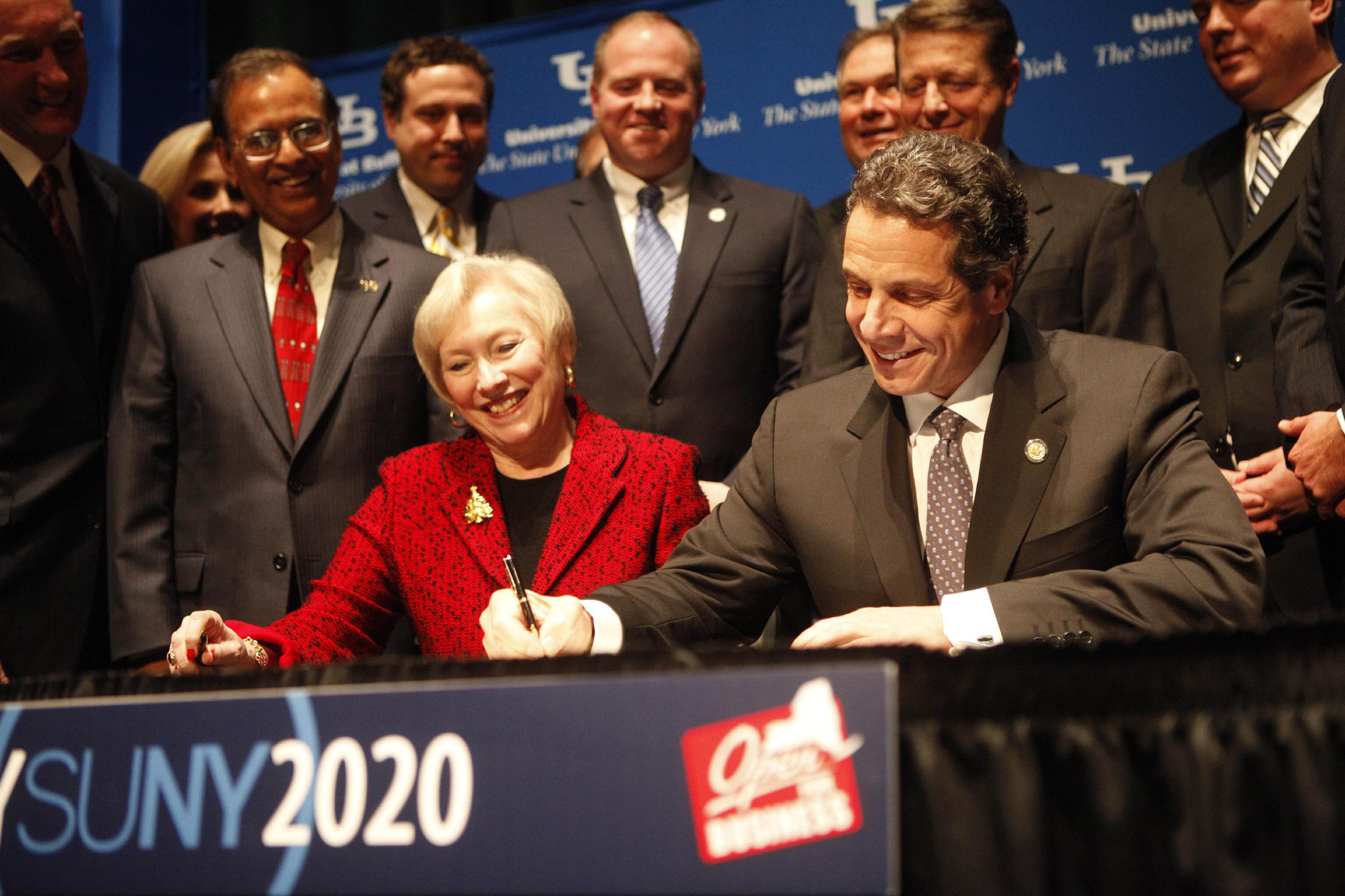 Surrounded by members of the Western New York delegation and UB President Satish Tripathi, left, New York Gov. Andrew Cuomo signs the NYSUNY2020 legislation during an event at the UB Center for the Arts, Tuesday, Dec. 13, 2011. Seated at the table with him is SUNY Chancellor Nancy Zimpher. (Derek Gee/Buffalo News)