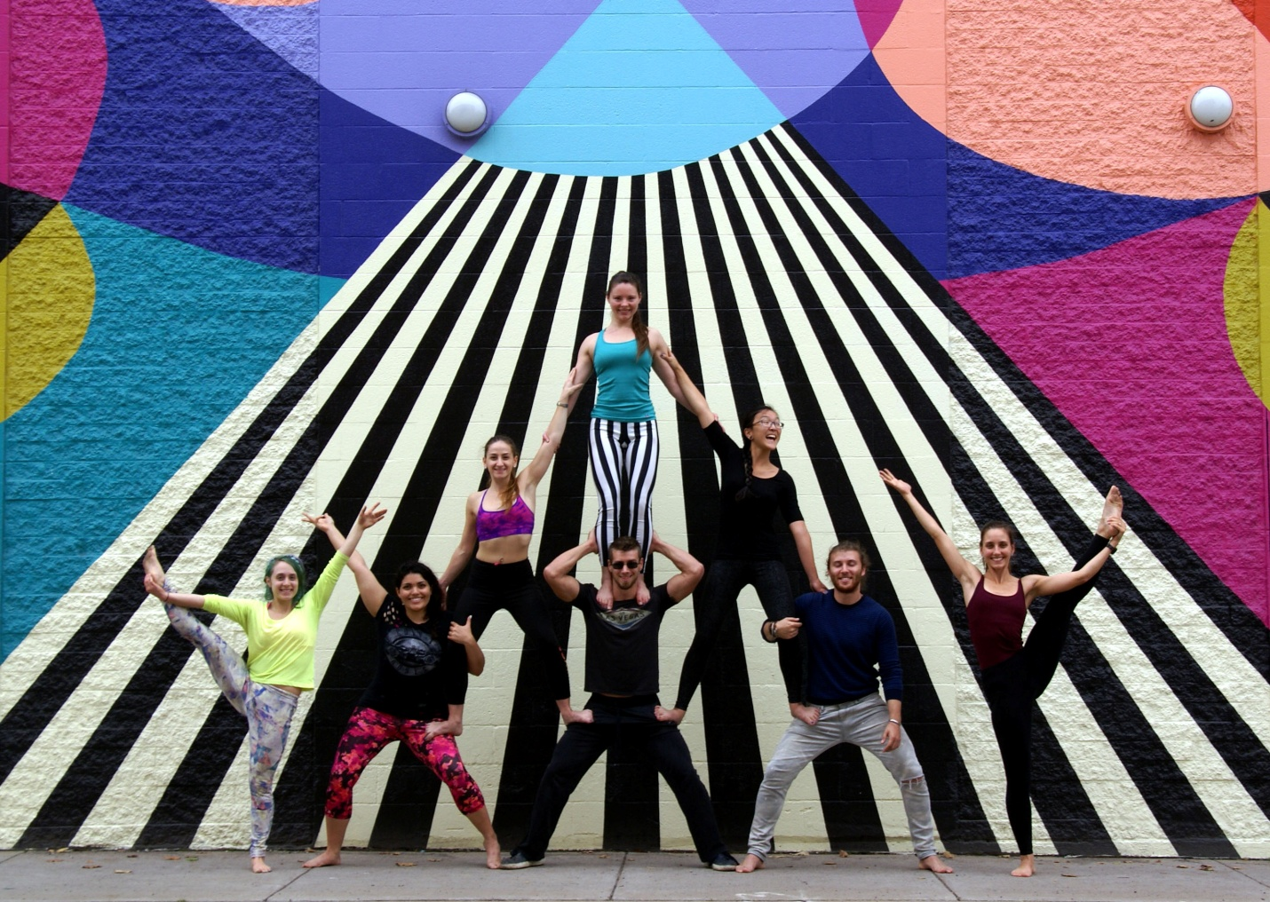 Members of Buffalo's AcroYoga community pose in front of a new mural on the north face of Shea's 710 Theatre.