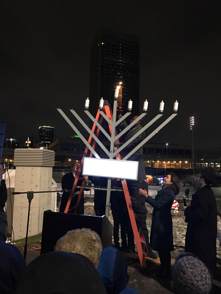 Mayor Byron W. Brown, center, lights a giant menorah at Canalside Thursday to celebrate Hanukkah with Lt. Gov. Kathy Hochul. (Matt Gryta/Buffalo News)