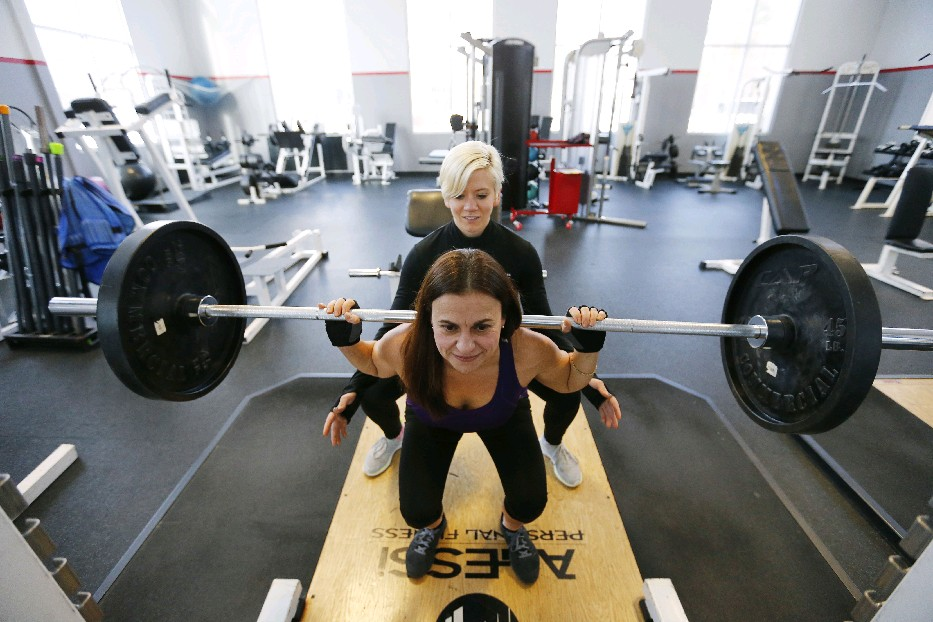 Trainer Erica Caso works with Diane Amerosa at Dr. Derek's Health & Fitness in Amherst. Amerosa laid out a weight loss plan in early 2014, dropped 40 pounds in 18 months and has maintained a healthier weight since. (Mark Mulville/Buffalo News)