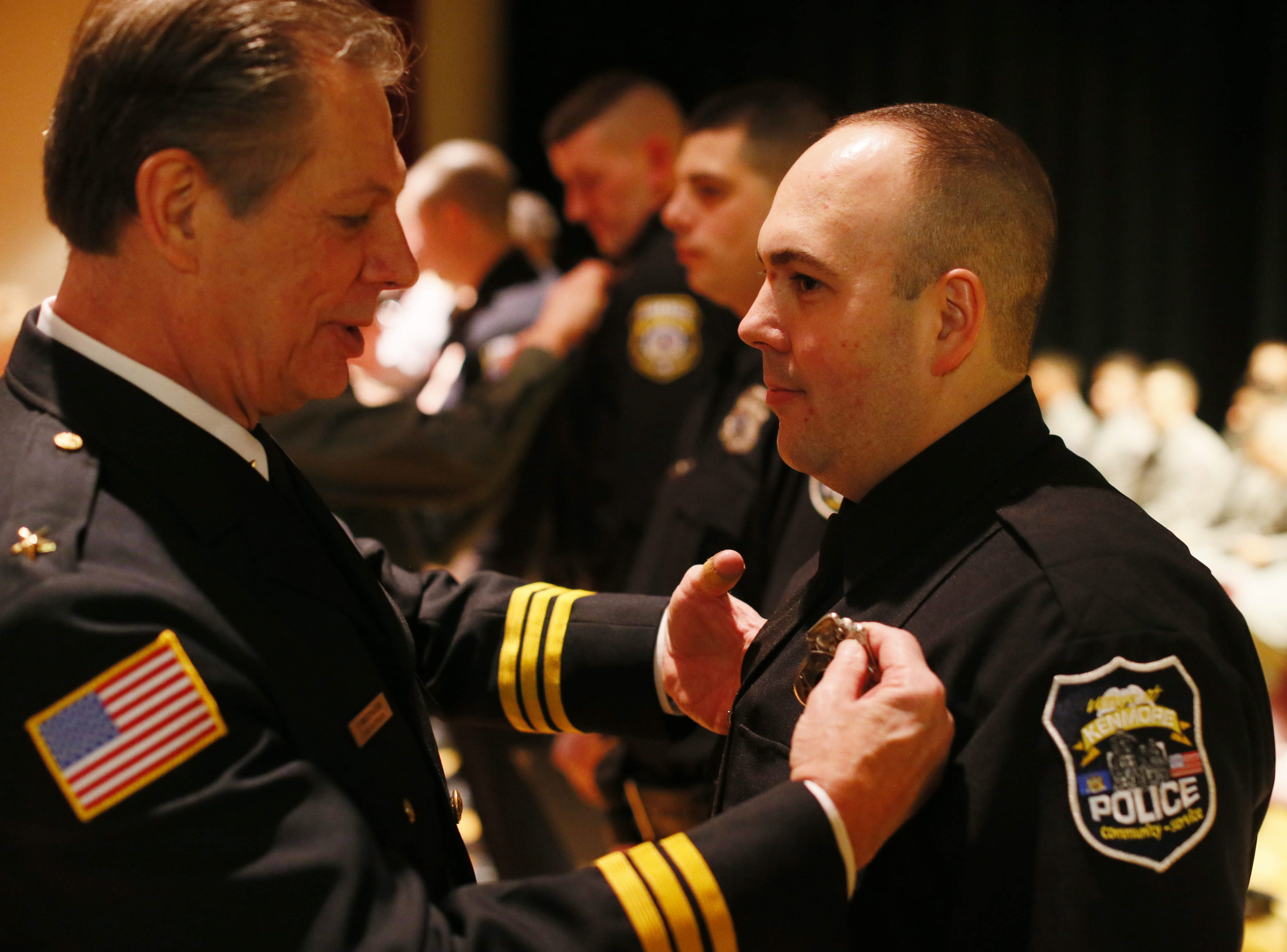 Kenmore Police Chief Peter Breitnauer, left, pins a badge on new police officer Joshua B. Davidson on Dec. 20, 2013, at the Erie Community College police academy graduation. (Derek Gee/Buffalo News)