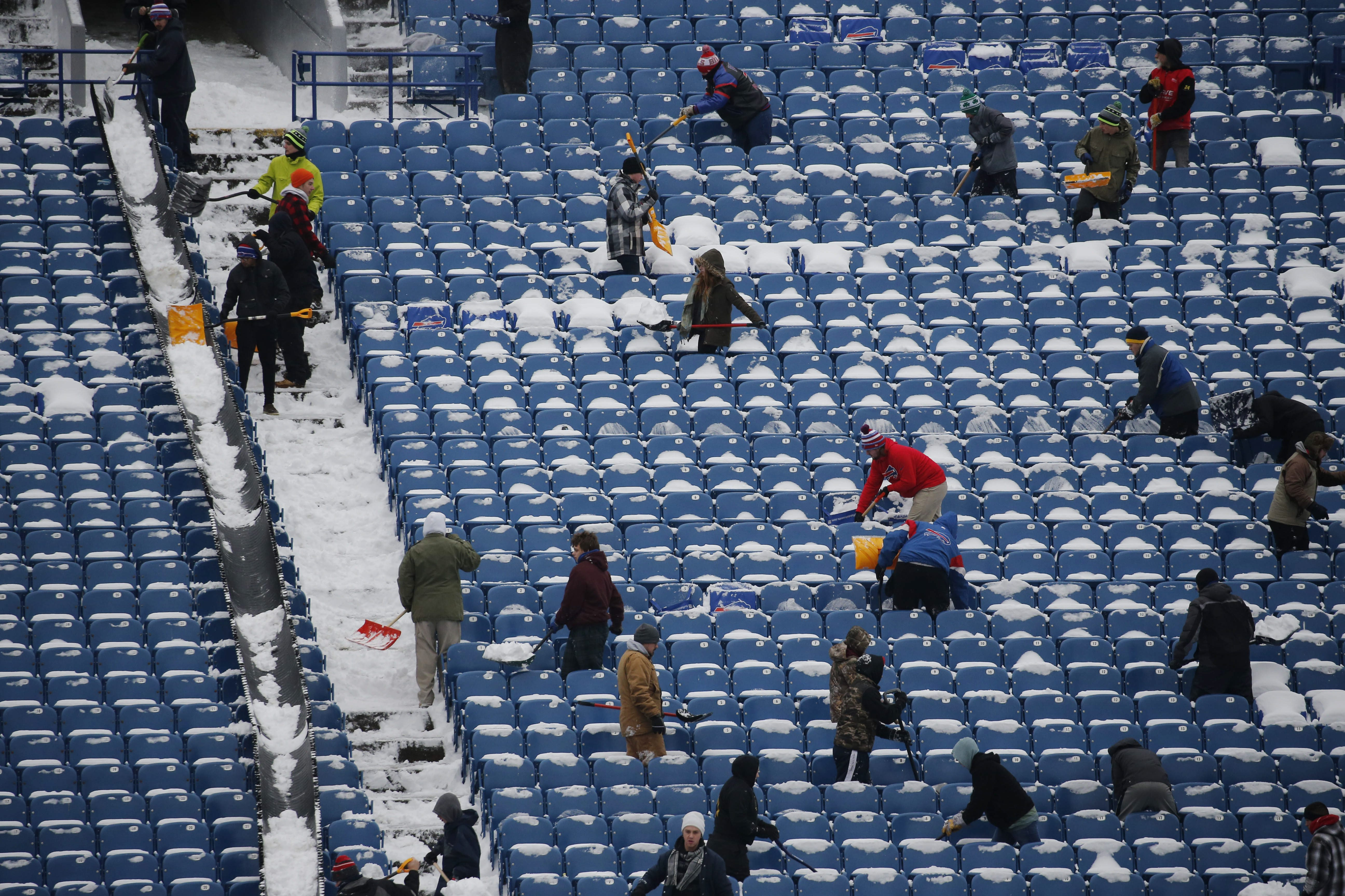 A shovel brigade clears snow from the stands in January at what was then Ralph Wilson Stadium in advance of the final game of the 2015-16 season. (Derek Gee/Buffalo News)
