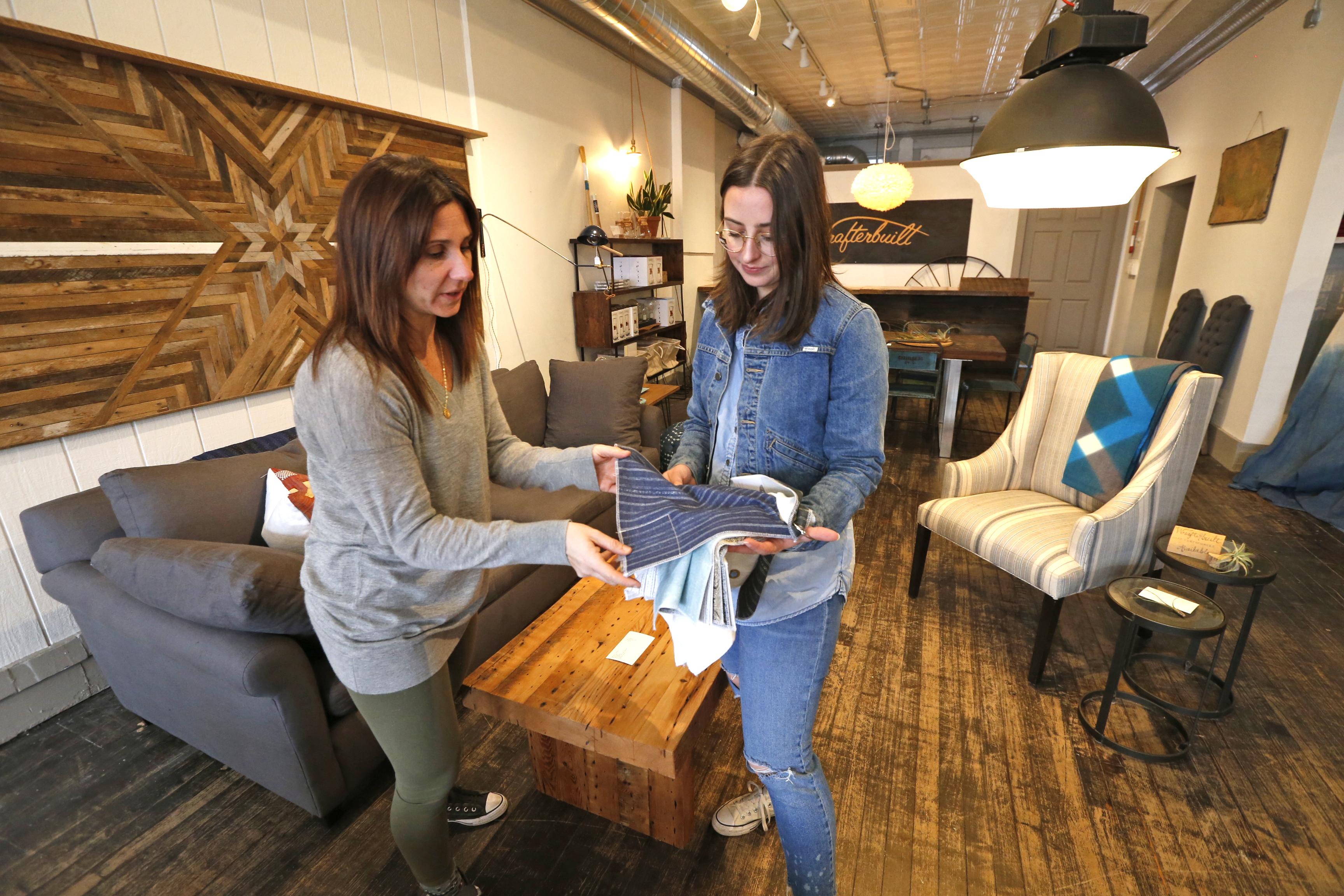 Bri Klejdys-Long, left, owner of Modern Nostalgia, and Jackie Wrafter, owner of Wrafterbuilt Furniture, examine fabrics in their shared space on Hertel Avenue. (Robert Kirkham/Buffalo News)