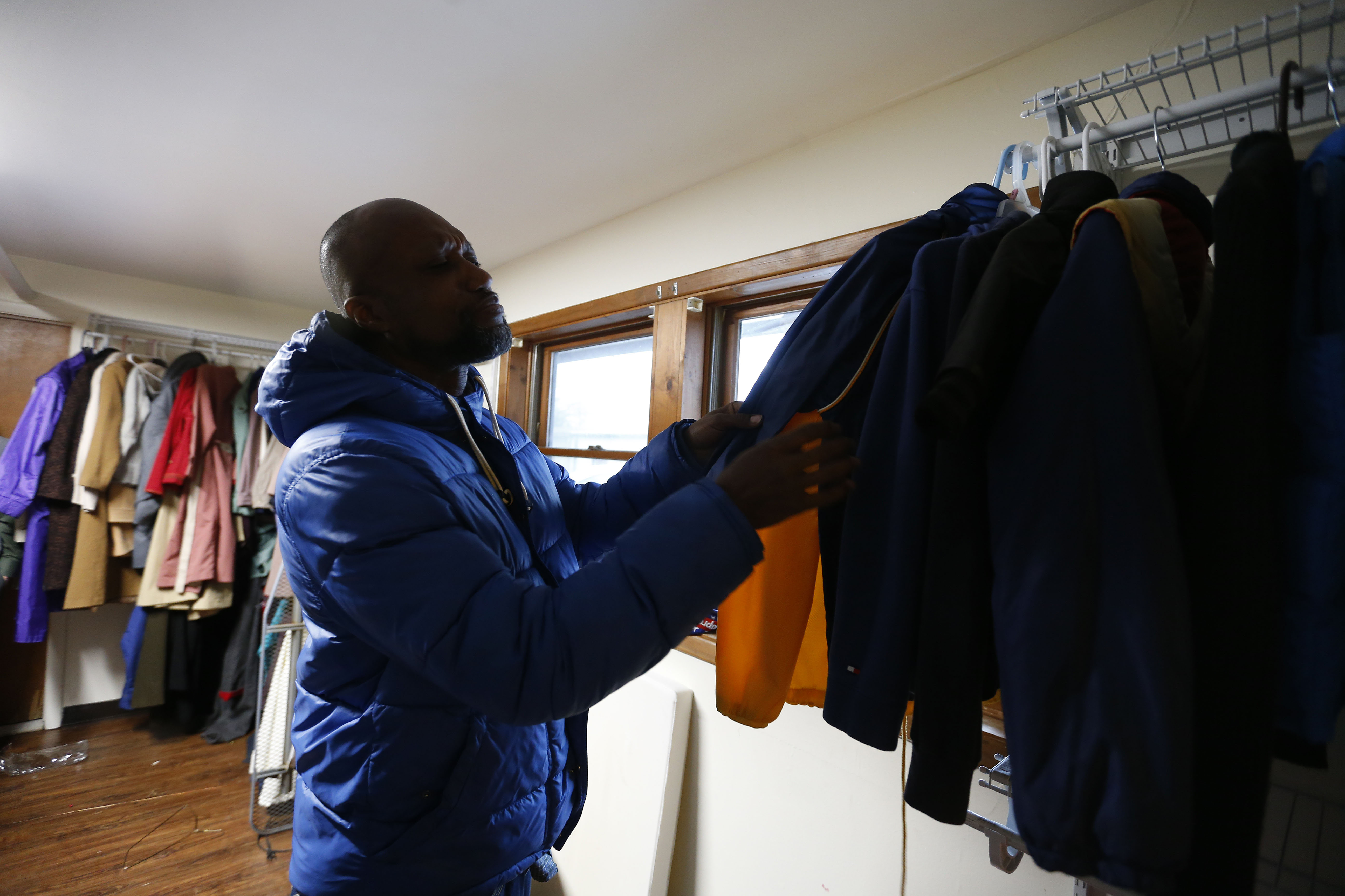 Chris Patterson looks for coats in the Clothes Closet at the Community Missions of Niagara Frontier in Niagara Falls, an agency with a long history of helping the poor.   (Mark Mulville/The Buffalo News)