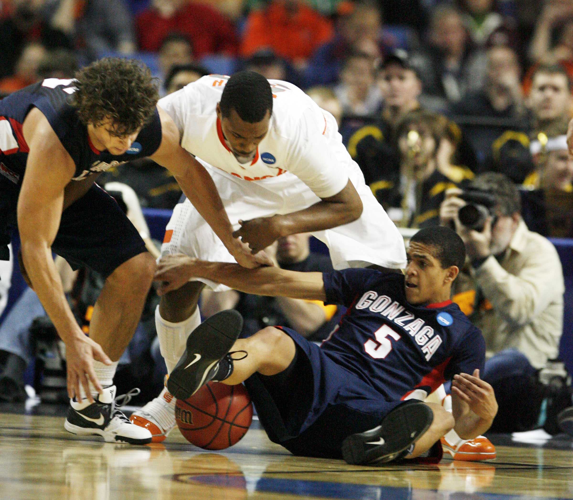 Syracuse forward Kris Joseph (32) dives for the ball along with Gonzaga guard G.J. Vilarino (5) and  Matt Bouldin. (James P. McCoy/Buffalo News)
