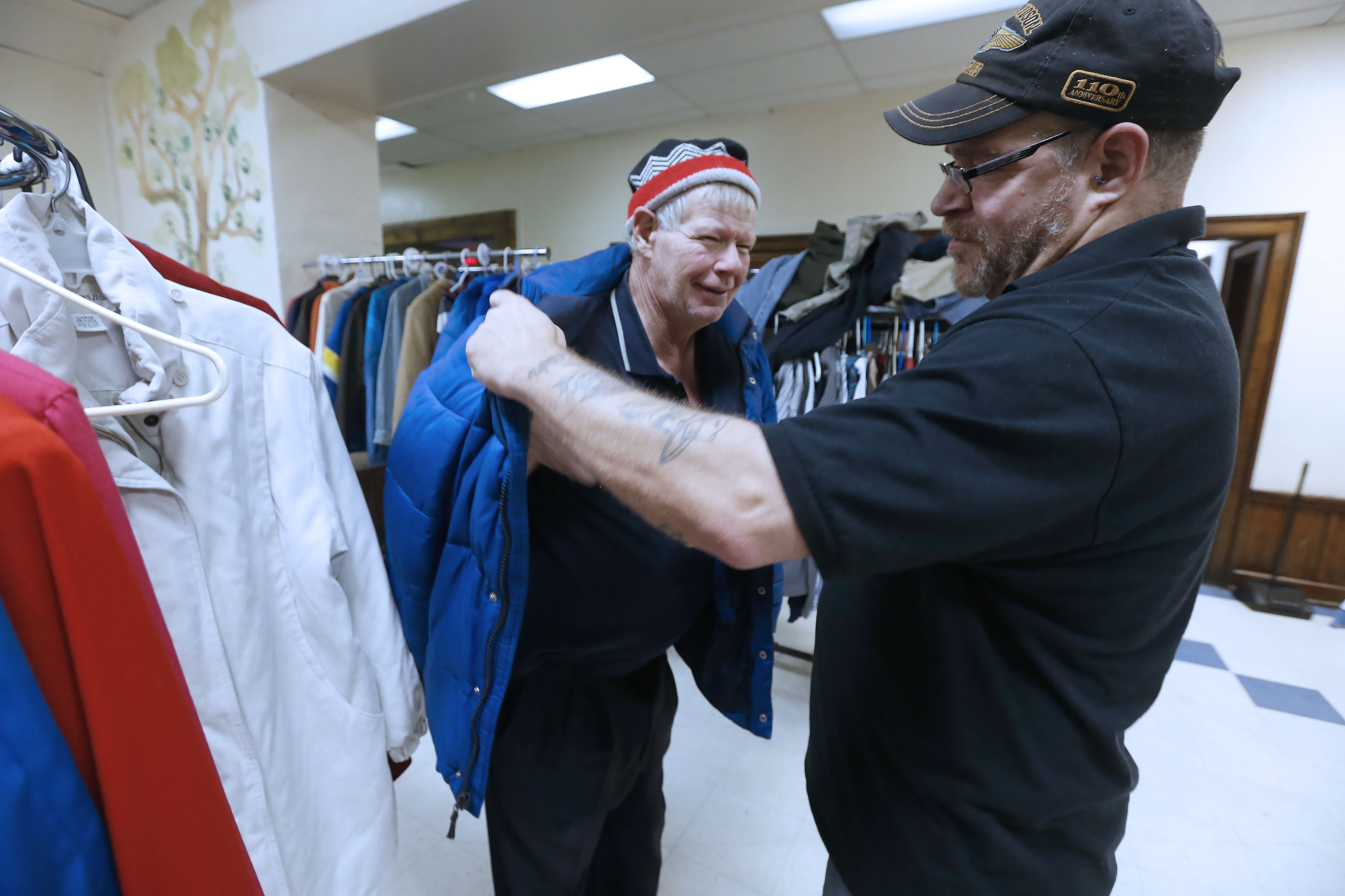 John Bornhoeft, right, building manager at Niagara Gospel Rescue Mission's shelter for homeless men, helps shelter resident Roger Sax pick out a free coat from racks at the facility on Tuesday, Jan. 3, 2017.  The mission recently received a $1.7 million grant to fix up the shelter for homeless men that it runs in the former YMCA building in Niagara Falls. (Robert Kirkham/Buffalo News)