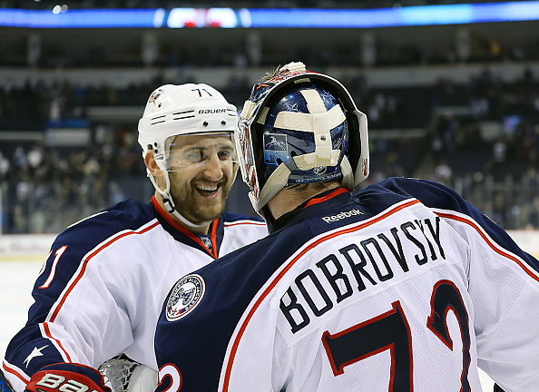 Nick Foligno (left) gives it up to goaltender Sergei Bobrovsky after Columbus won its 14th straight game Dec. 29 in Winnipeg (Getty Images).