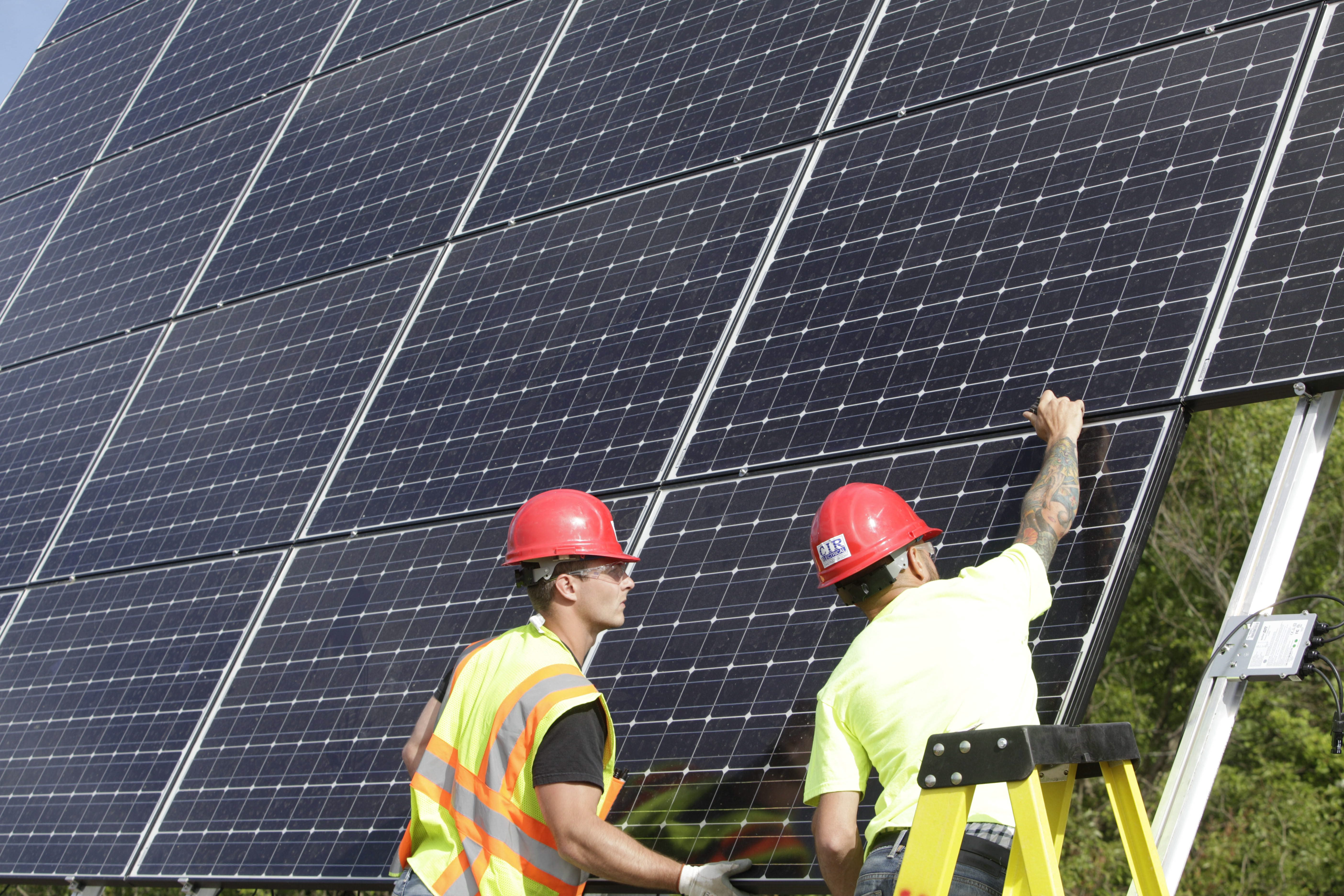 """Edward Sarcione, left, and electrician Joe Kilijanski of CIR Electrical Construction Corp. install an array of solar panels made by Silevo on a """"tracker"""" system that automatically follows the sun to optimize the system's performance at a residence in Marilla, Friday, June 20, 2014.  (Derek Gee/Buffalo News)"""