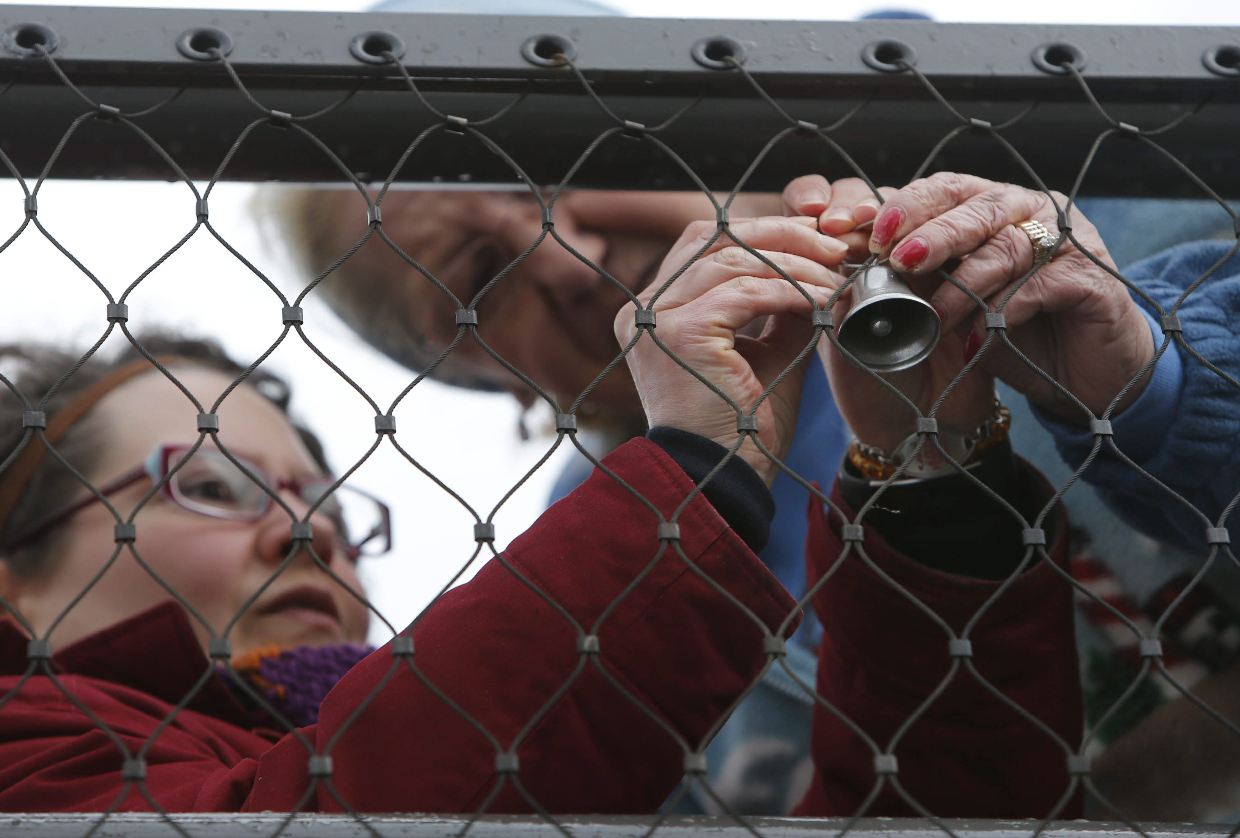 Cancer survivors Heather Fraccica of Depew, left, and Jean Hall of South Buffalo hang a bell on the Commercial Street Bridge at Canalside, after it was dedicated as the Roswell Park Cancer Institute Bridge of Hope, in March 2016. (Derek Gee/Buffalo News file photo)