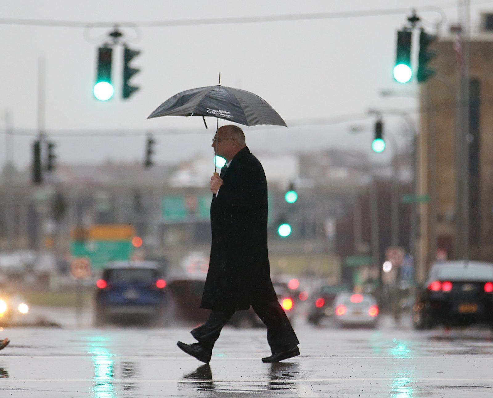 A pedestrian crosses North Division Street at Main Street in Buffalo on a rainy afternoon, Tuesday, Jan. 3, 2017. (Sharon Cantillon/Buffalo News)
