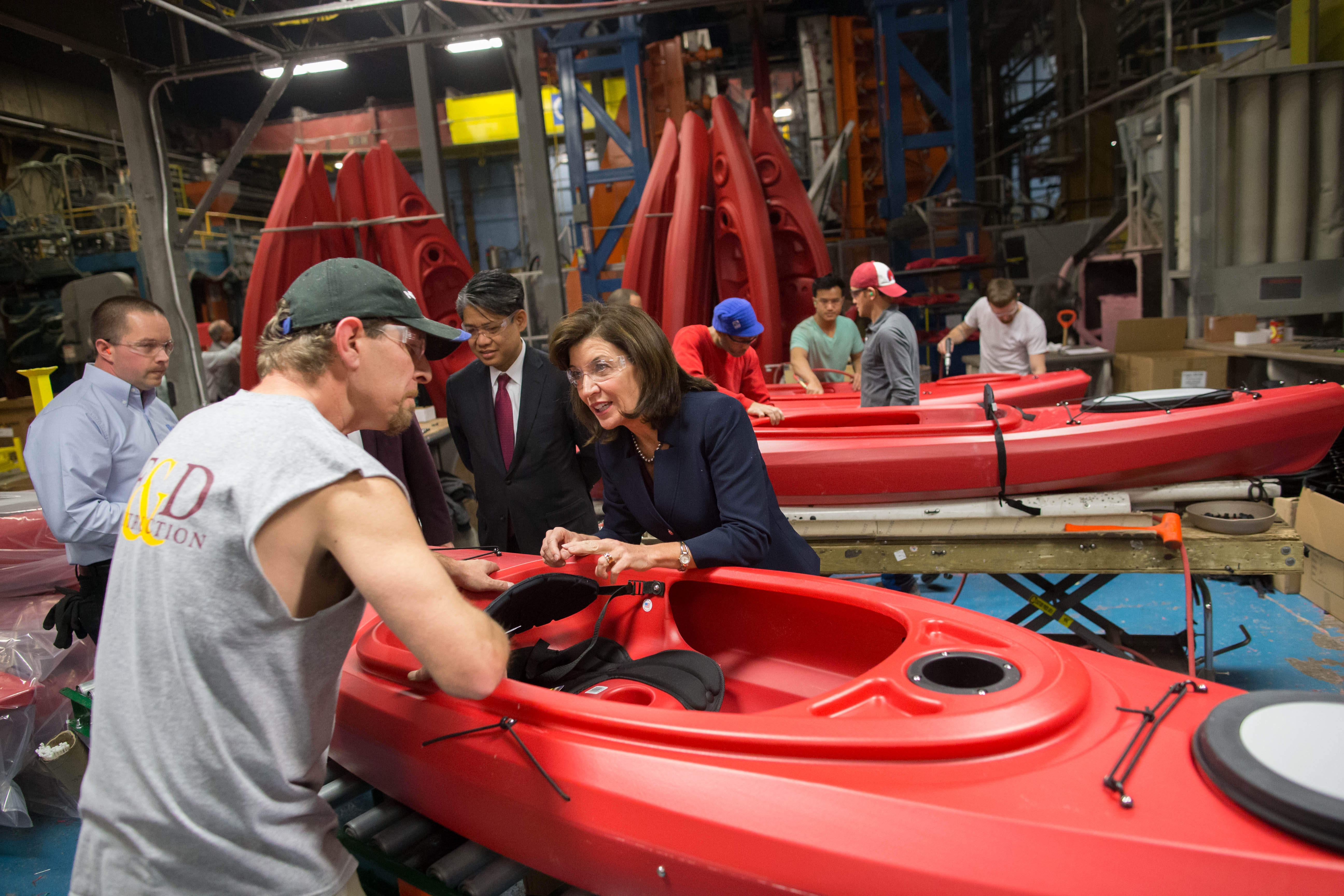New York Lt. Gov. Kathy Hochul stops to chat with assistant foreman Dwayne Cragle during a tour of the company's facility in North Tonawanda on  Thursday. The company, which makes a wide variety of plastic goods, like these kayaks, using blow molding technology, recently completed a $3 million expansion project thanks in part to a low-cost hydropower allocation from NYPA's Niagara Power Project.  (Derek Gee/Buffalo News)