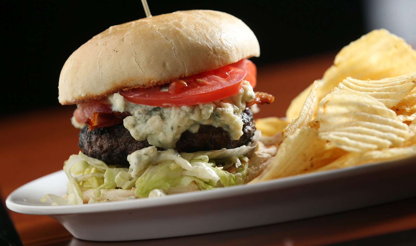 Rock Bottom's The Raging Cajun Burger is a half-pound burger blackened Cajun style and grilled then topped with bacon, creamy bleu, lettuce and tomato. (Sharon Cantillon/Buffalo News)